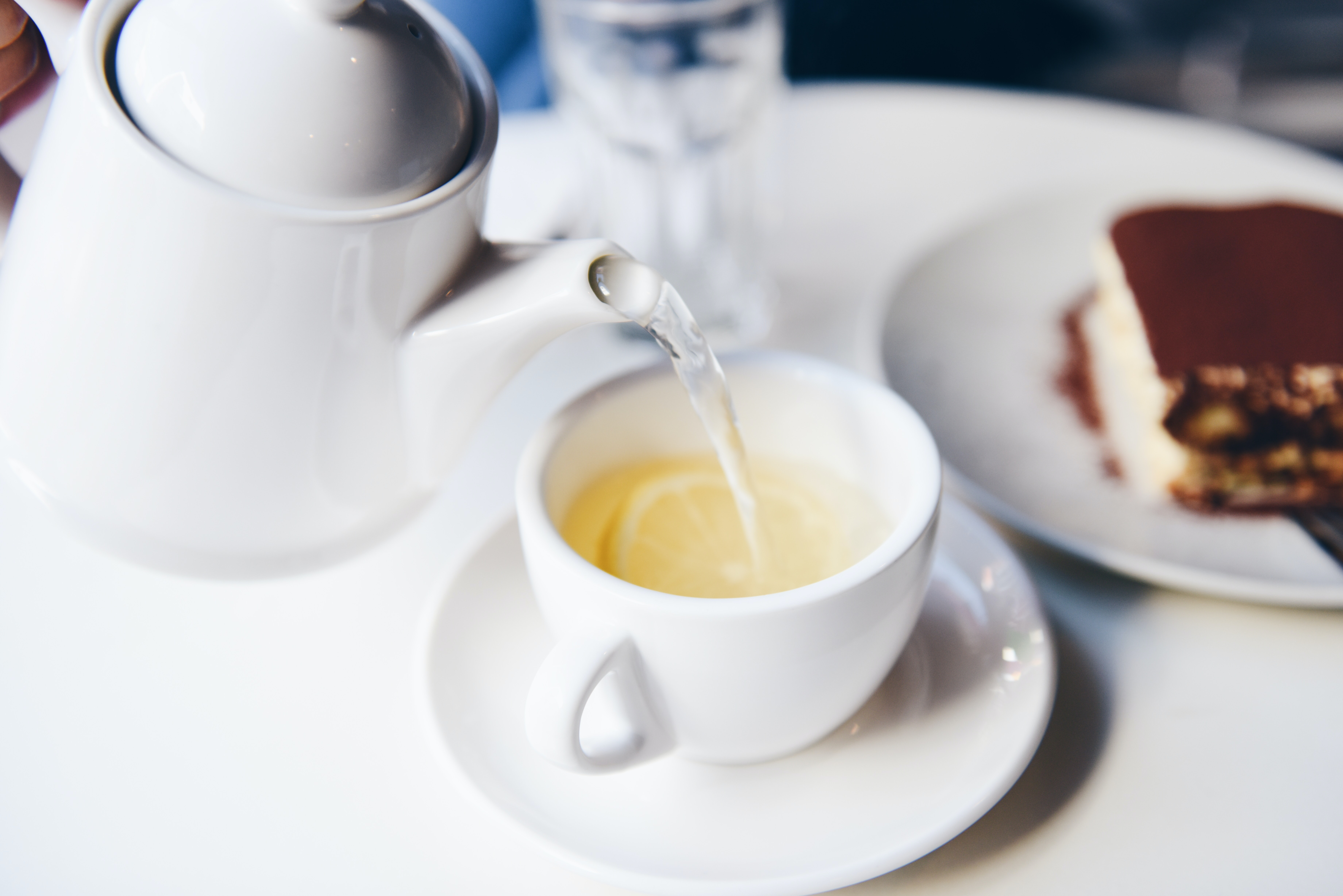 A person pouring a cup of tea into a teacup that has a lemon inside of it