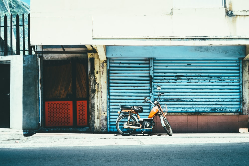 orange motorcycle near blue shutter gate