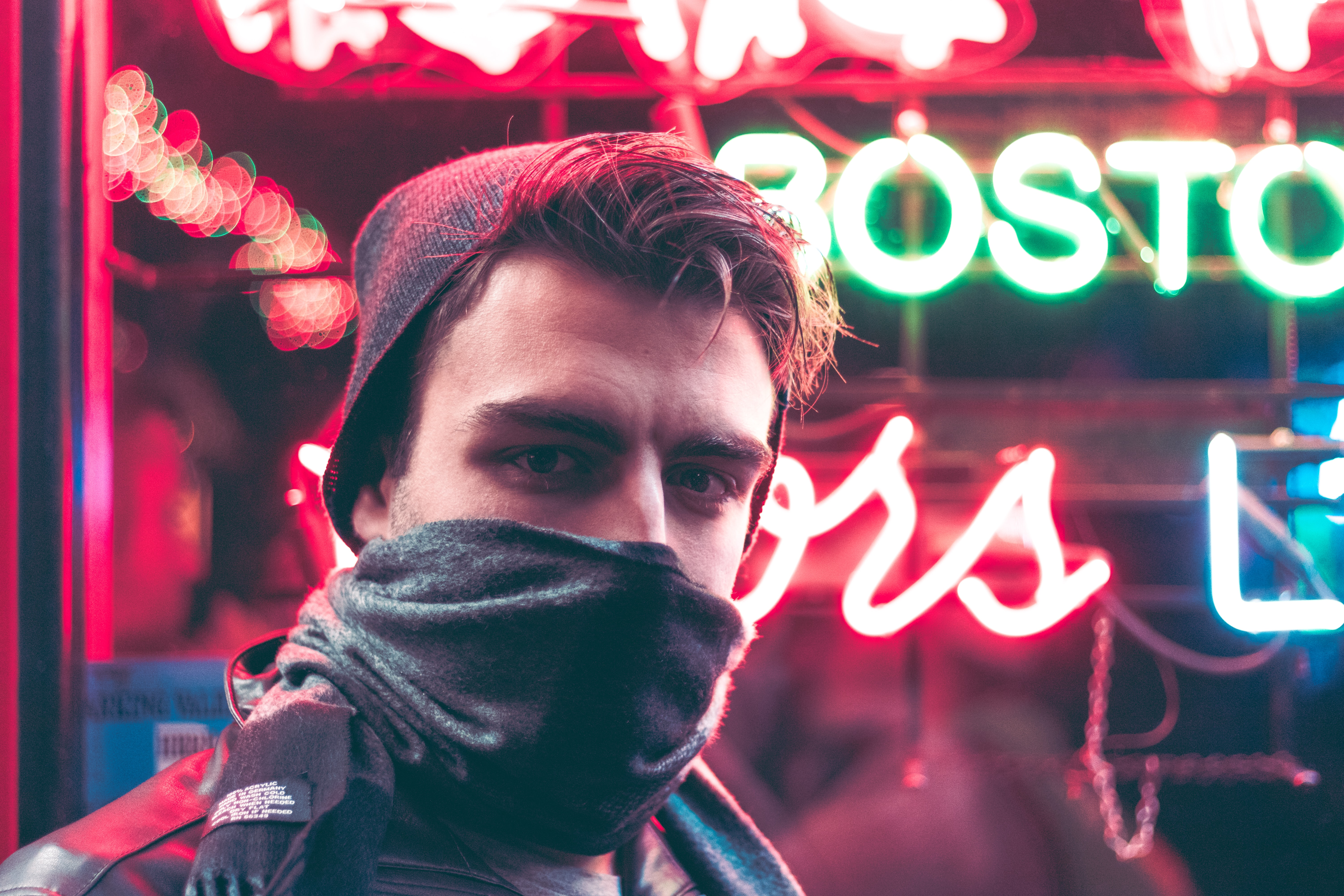 man with face half covered with mask standing in front of red and green neon light signage during daytime