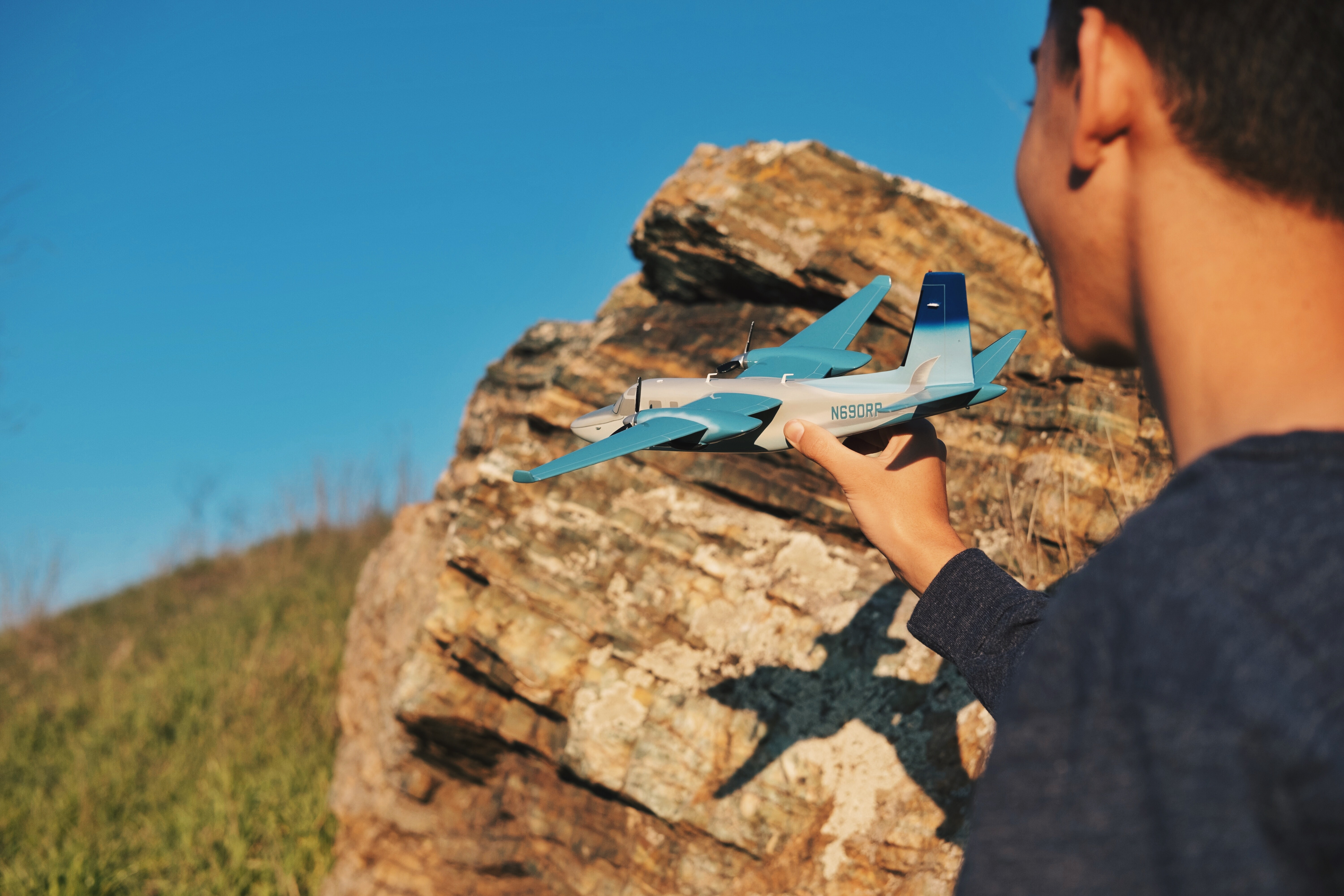 A boy holds a model airplane, casting a shadow on a rock before a blue sky