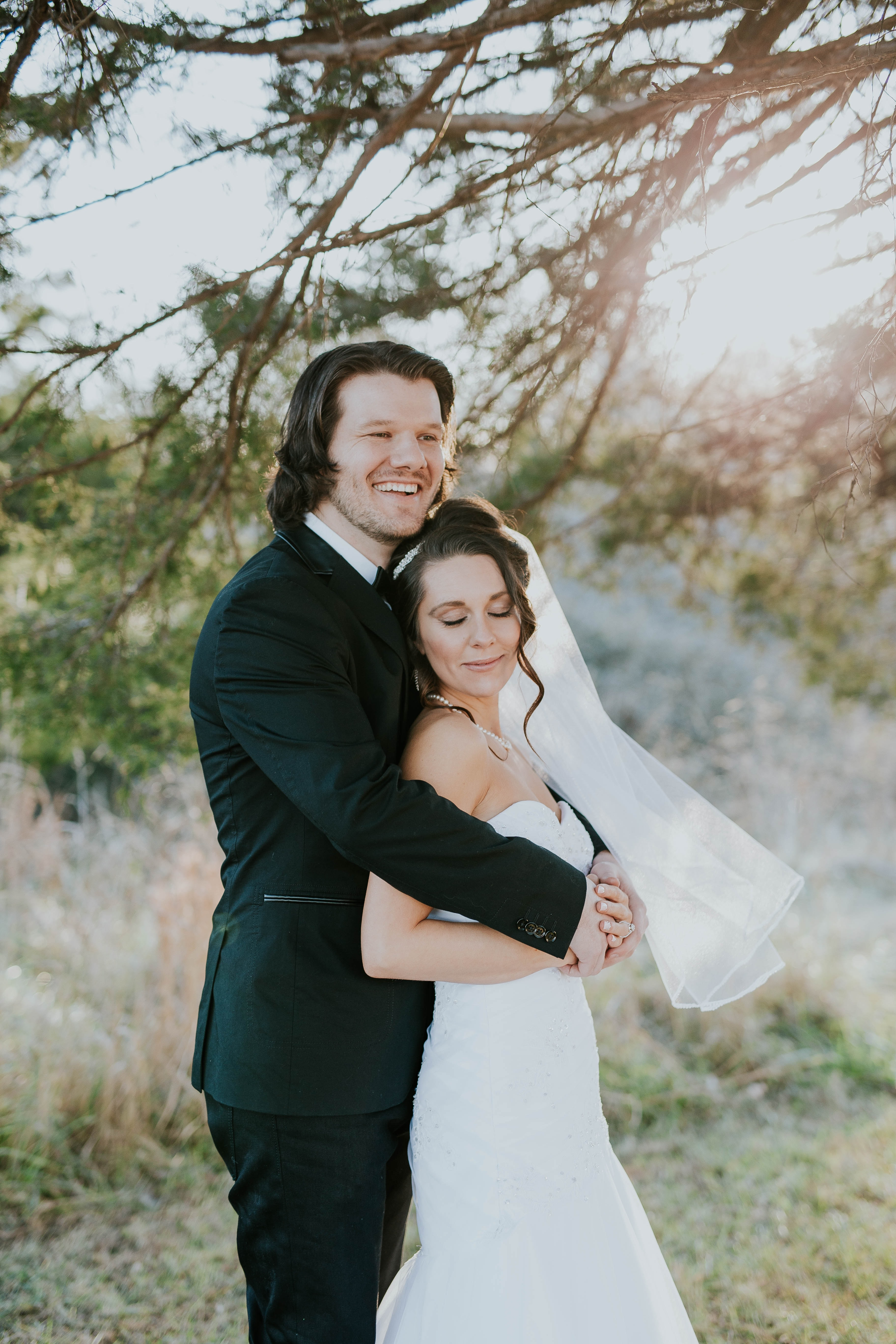 A bride in her wedding dress and groom in a suit embrace in a sunny meadow.