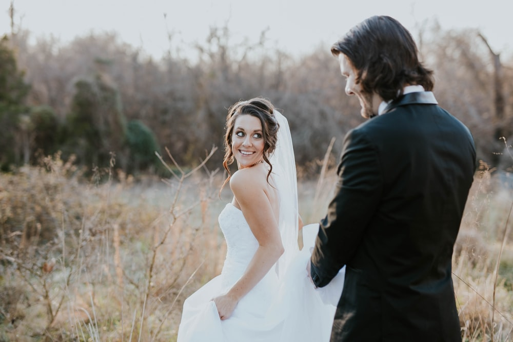 woman in white wedding dress and man in black suit jacket