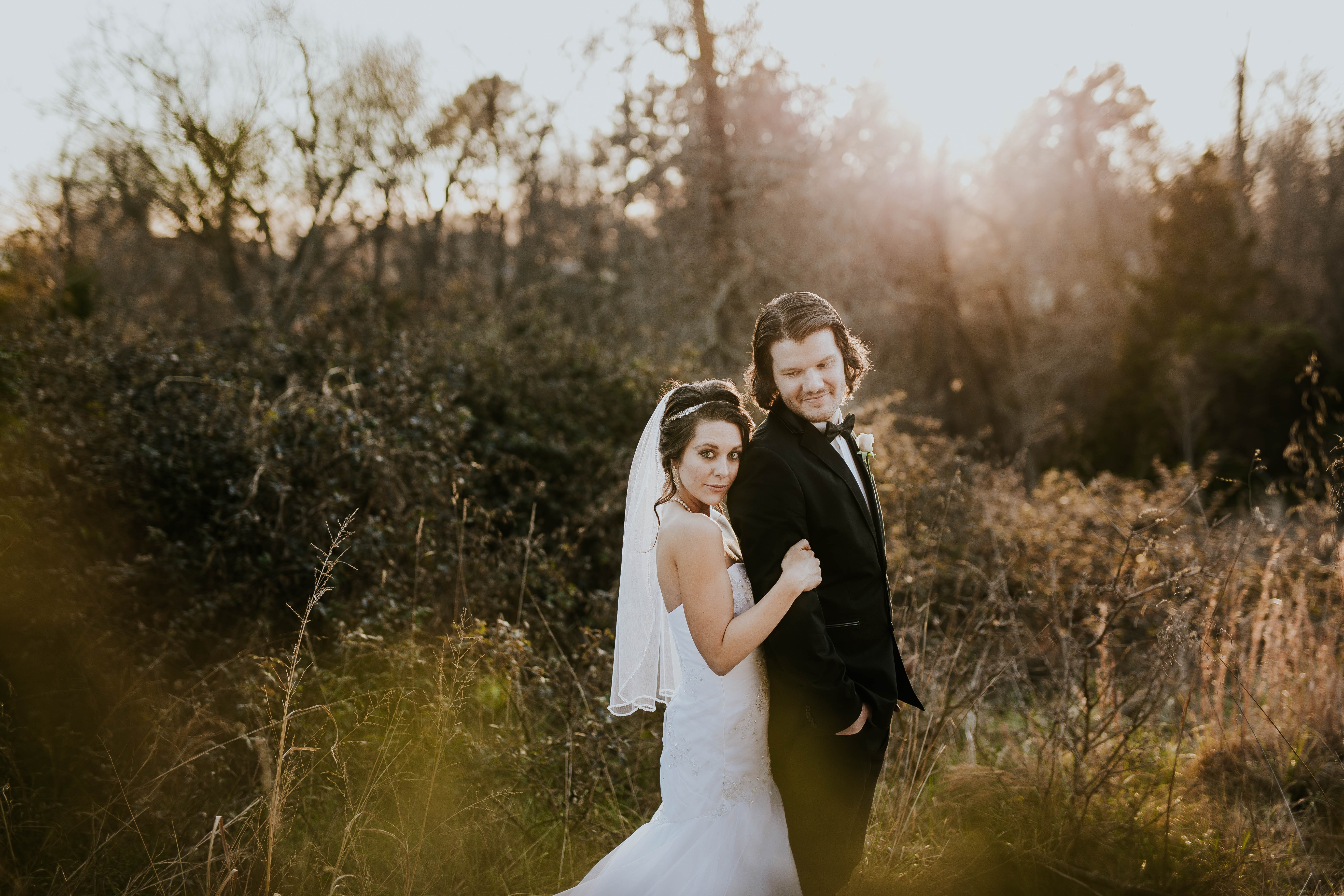 bride and groom near green leafed plants during daytime