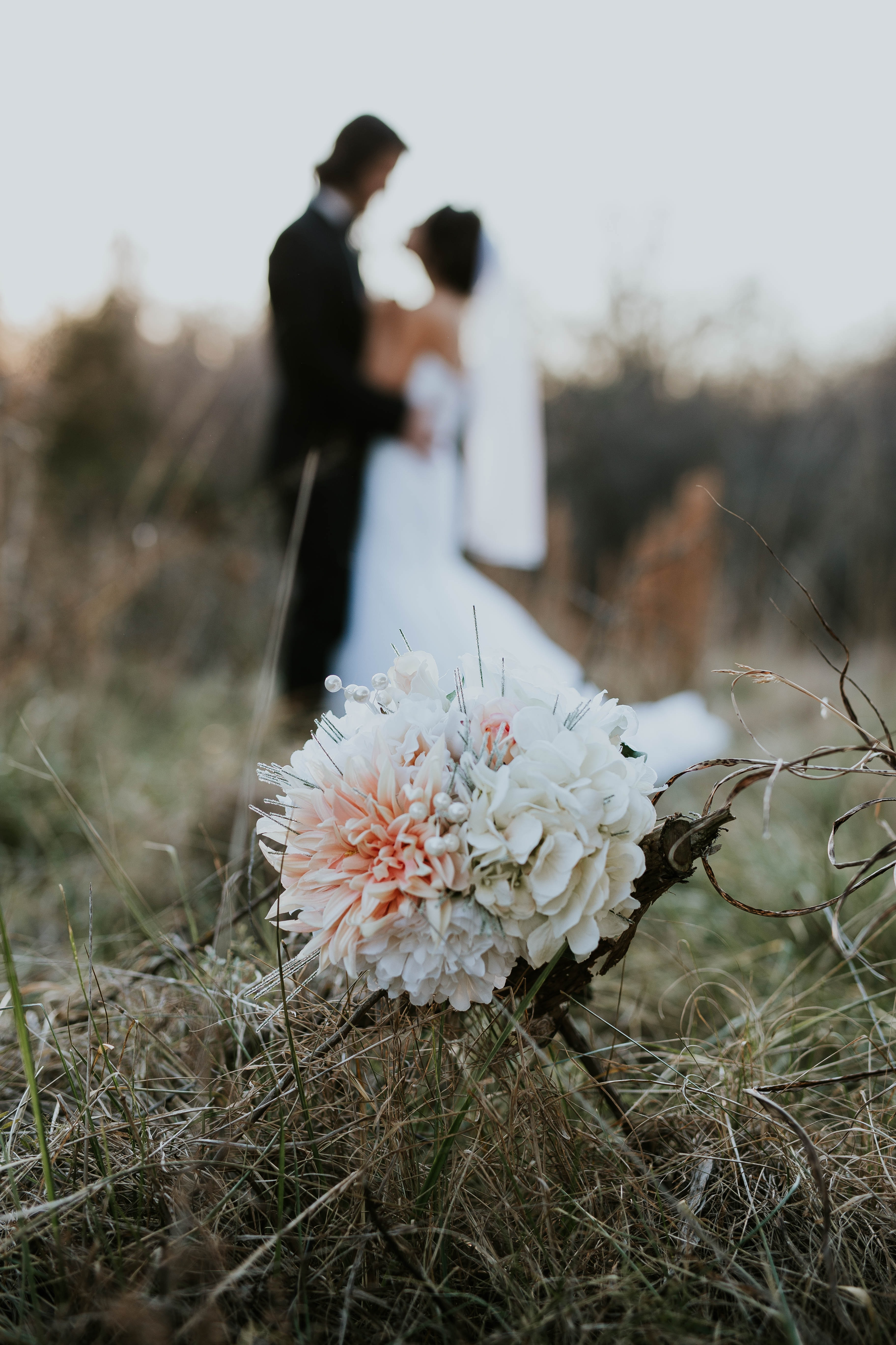 A bouquet sits in tall grass while a married couple embraces in the fuzzy background