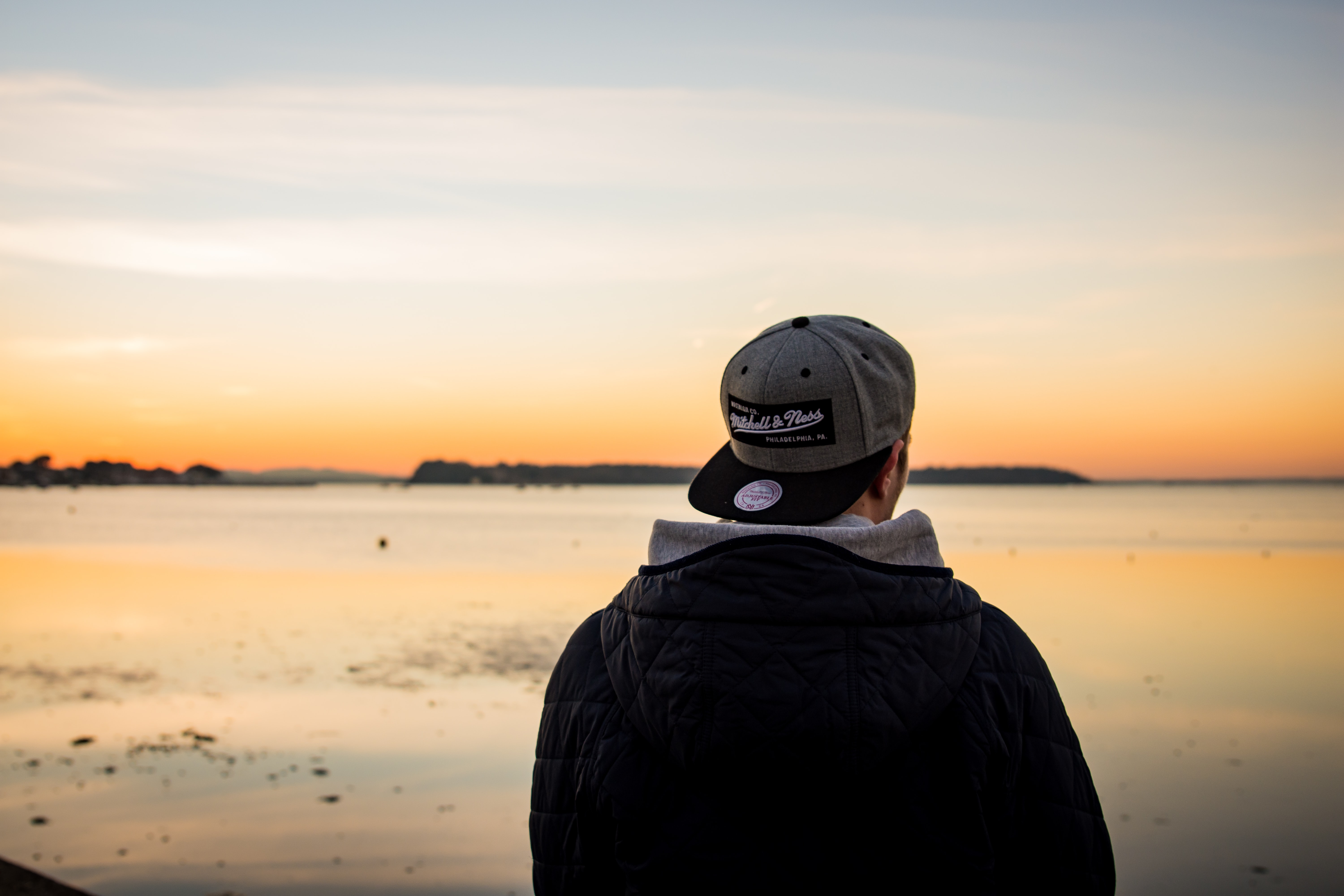A male wearing a cap and coat looks out to sea at Sandbanks during dawn-or-dusk