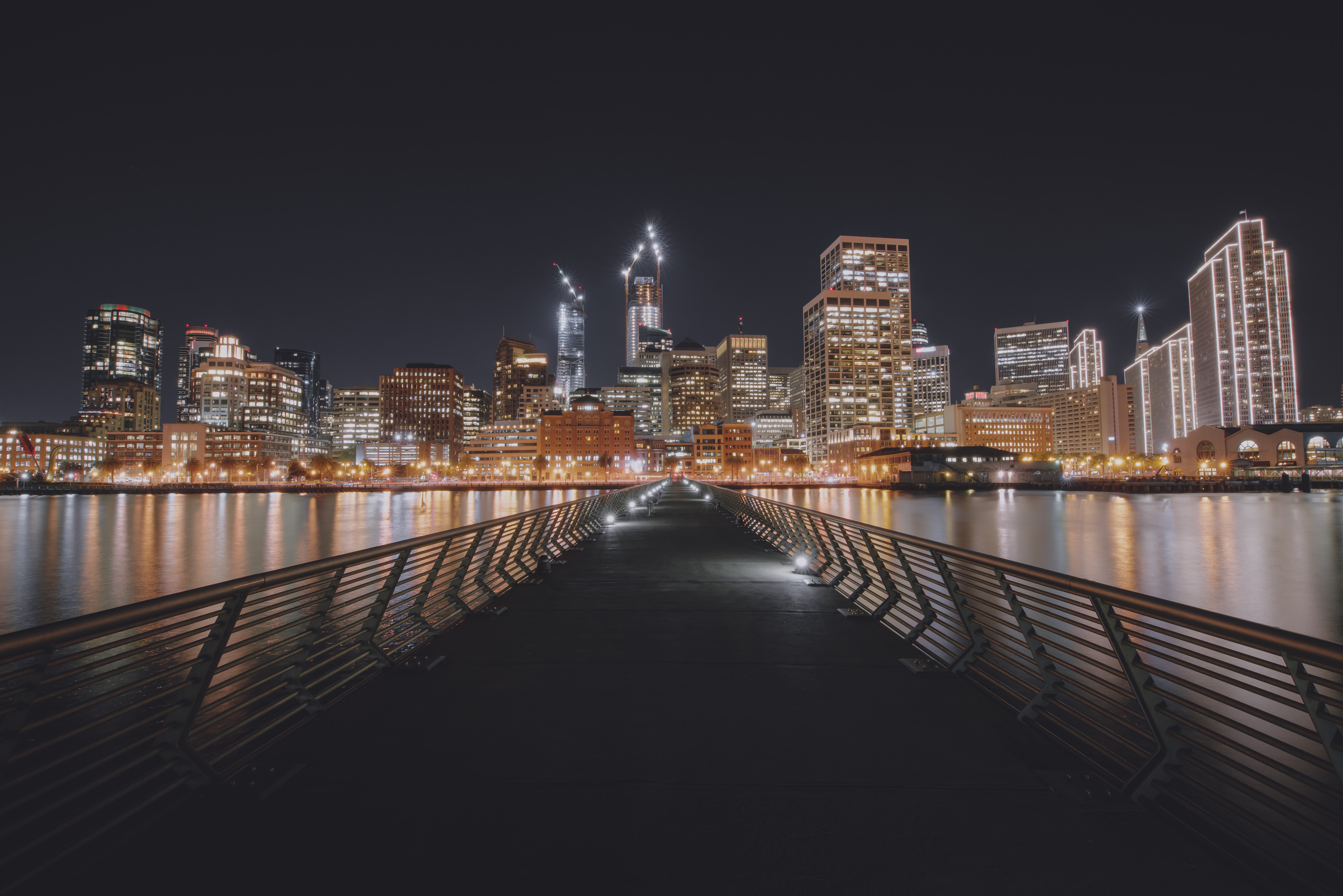 A look down Pier 14 with cityscape lighting reflections in the surrounding water