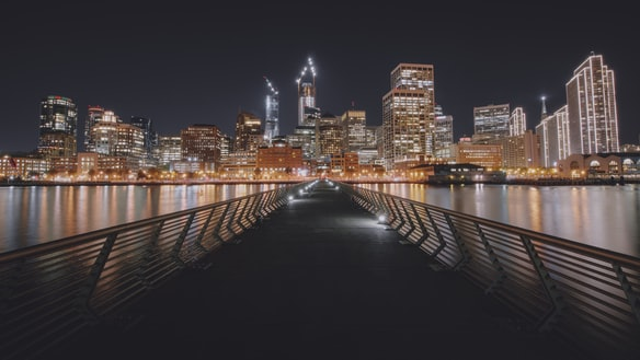 Pier 14 at night, looking towards downtown San Francisco's brightly lit buildings
