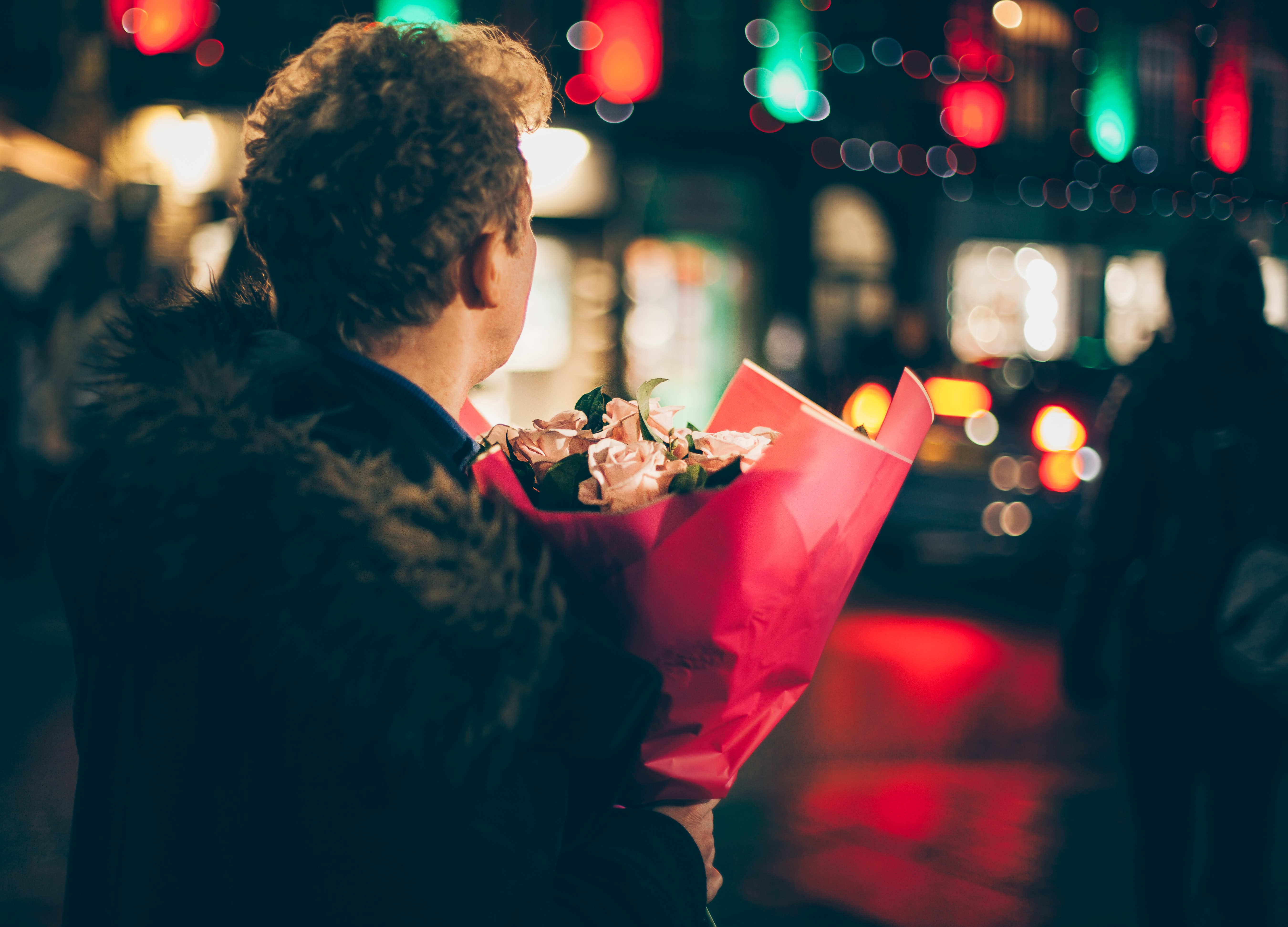 A man holding a bouquet of pink flowers awaits his date in Camden Town at night