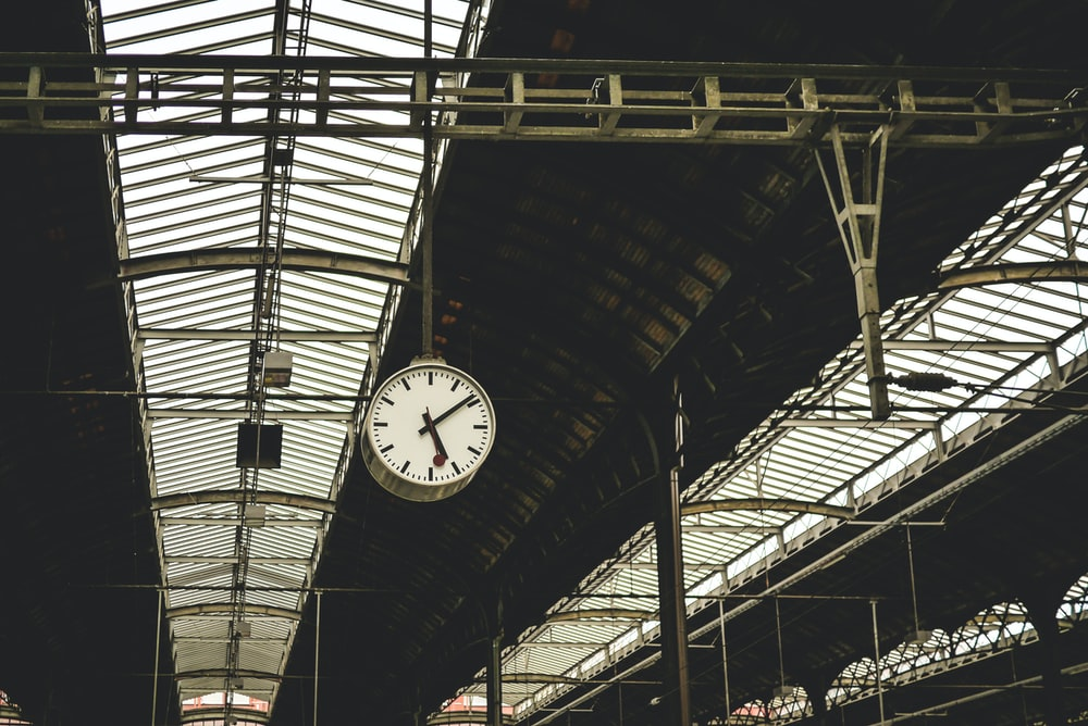 A clock hanging on the train station platform.