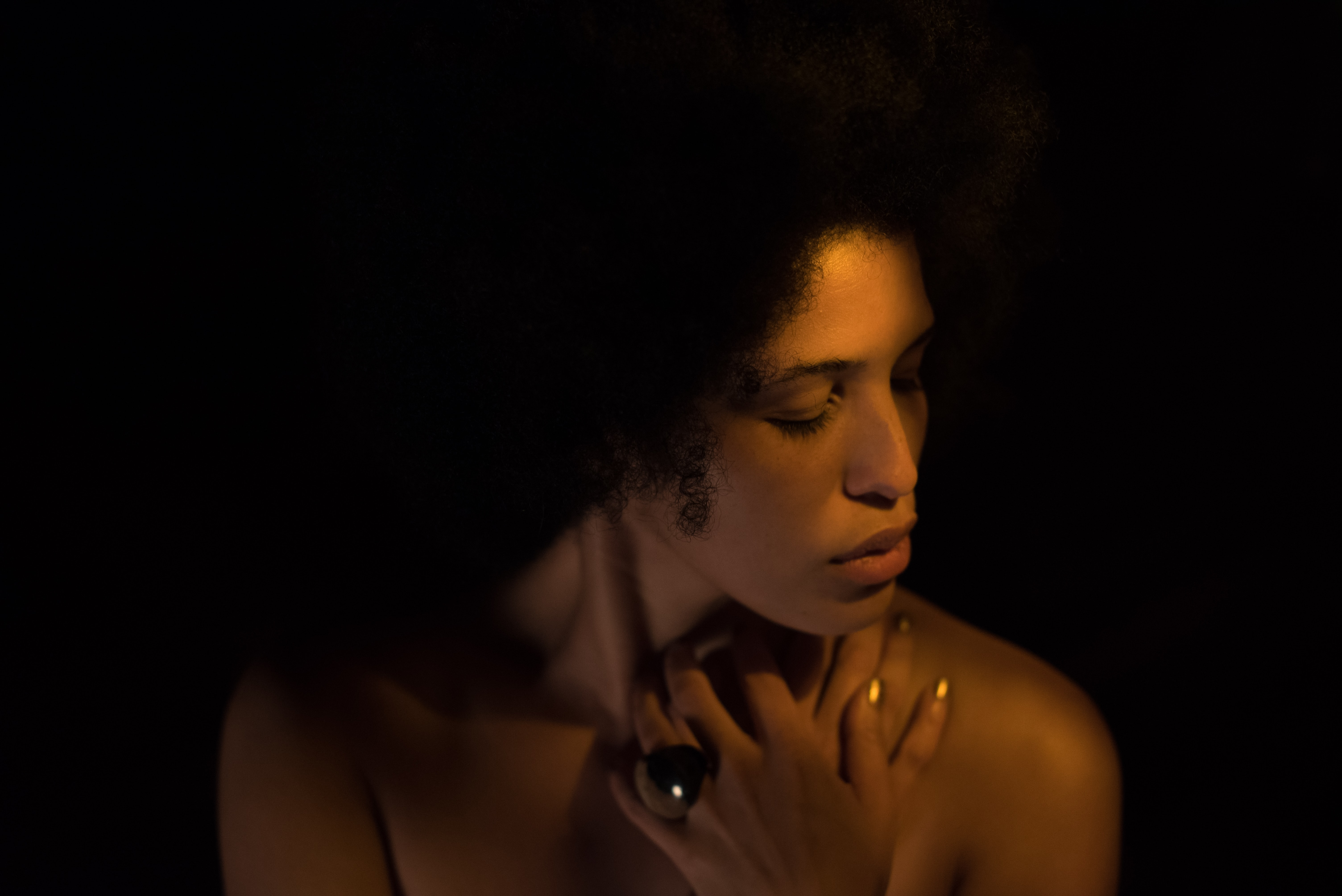 Woman wearing ring with curly hair poses in dark lighting with eyes closed a