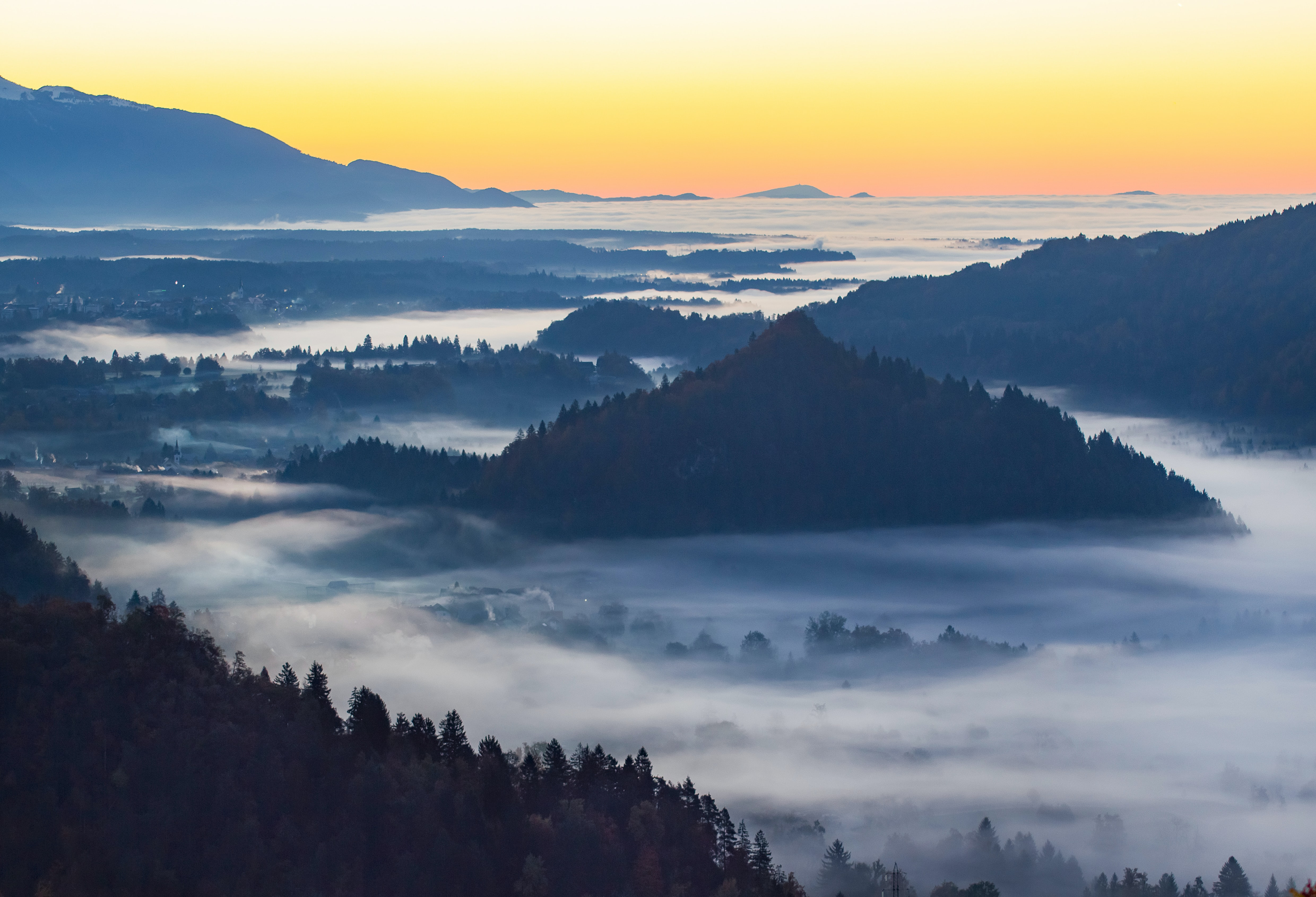 Mist over a town in a mountain valley in Bled during sunset