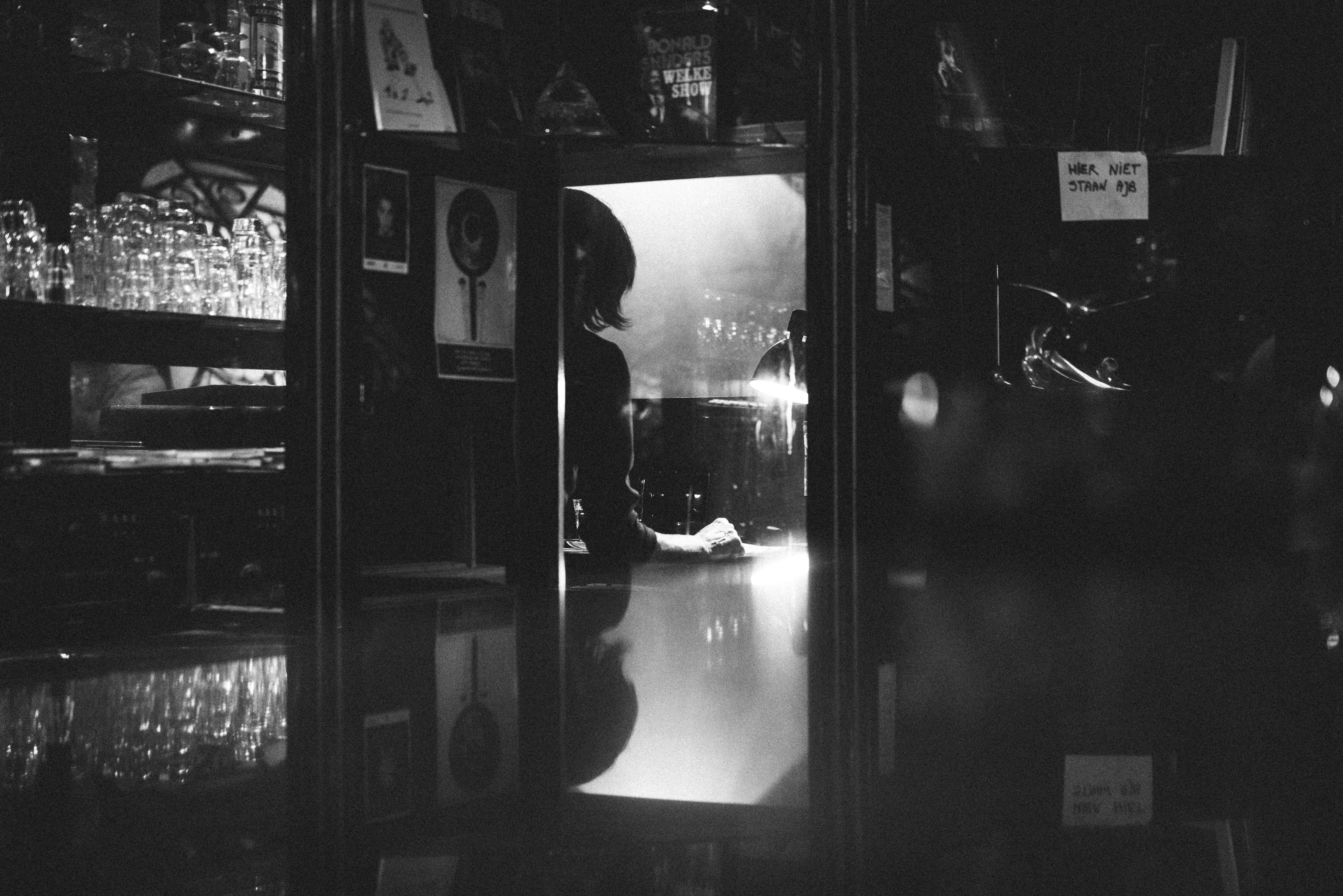 A black-and-white shot of a bar and a female cashier in Amsterdam.