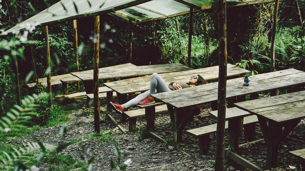 woman lying on gray wooden picnic table