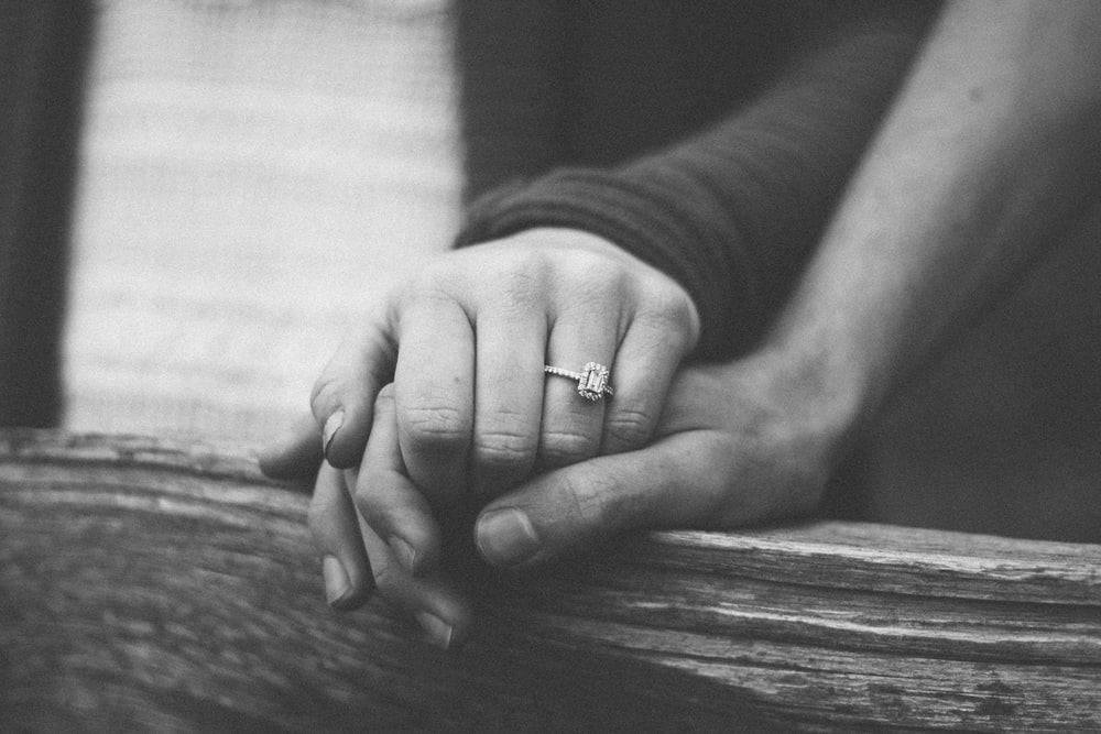 a couple holding hands with a wedding ring visible