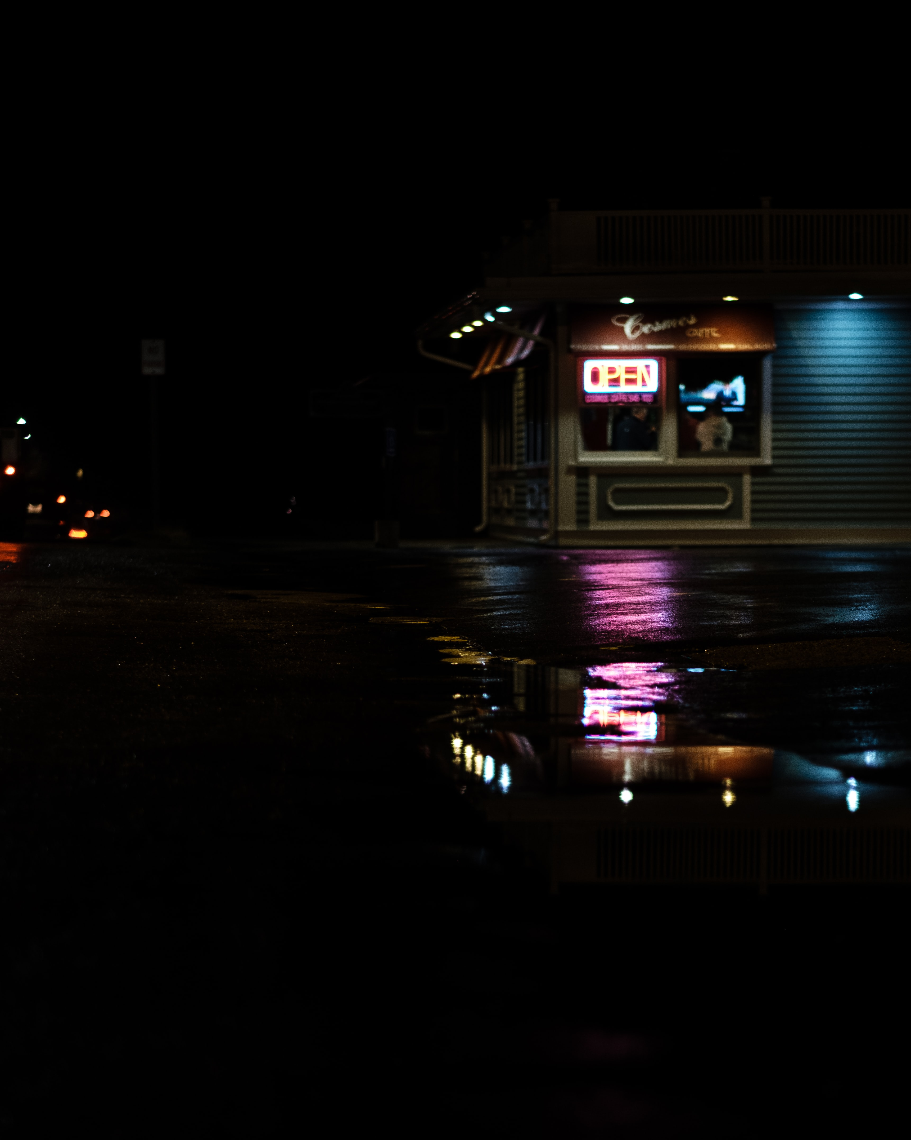 A store in the dark and a puddle reflecting the neon lights from the storefront window