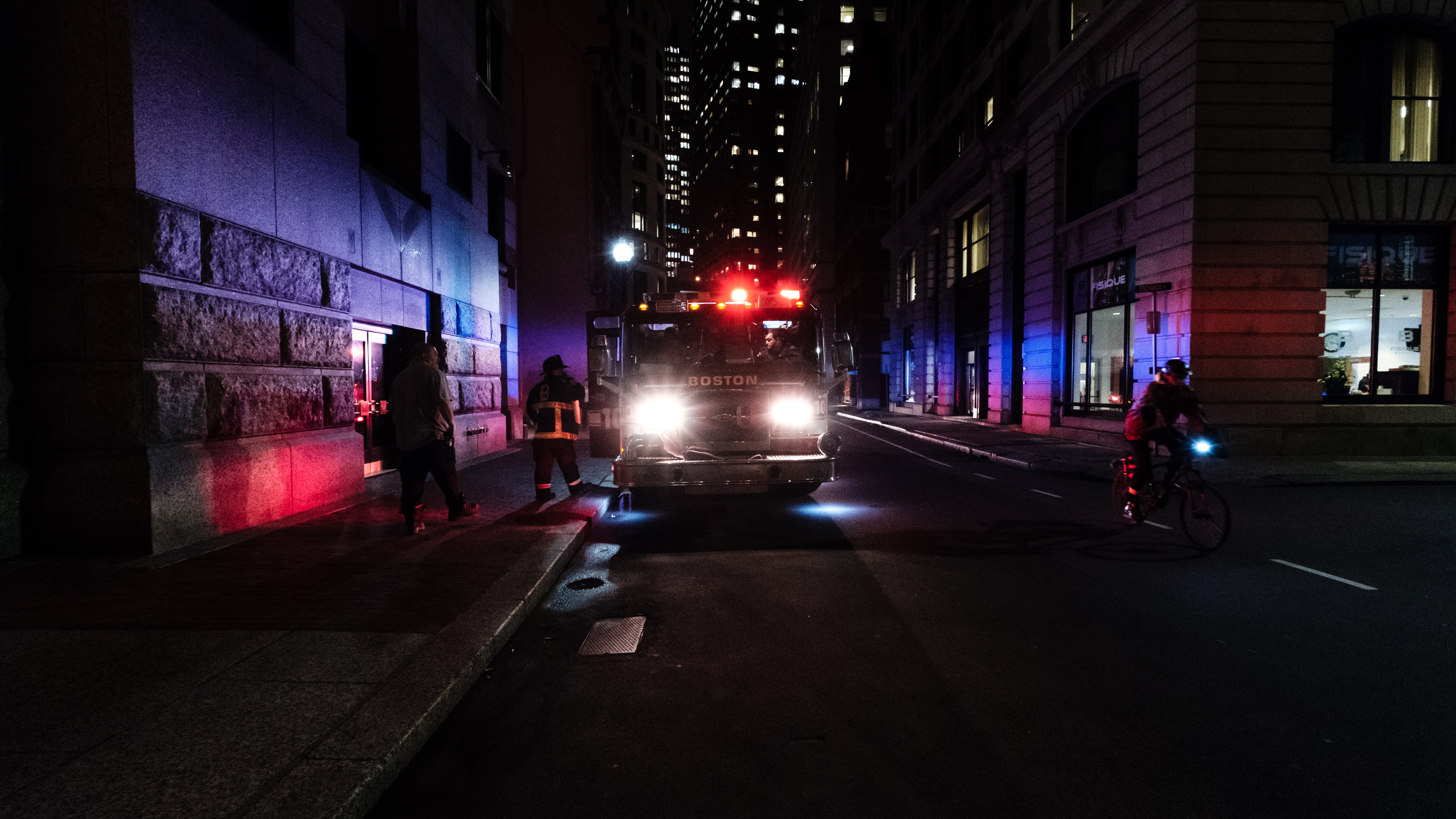 Red emergency lights of Boston firefighter truck parked on a street at night
