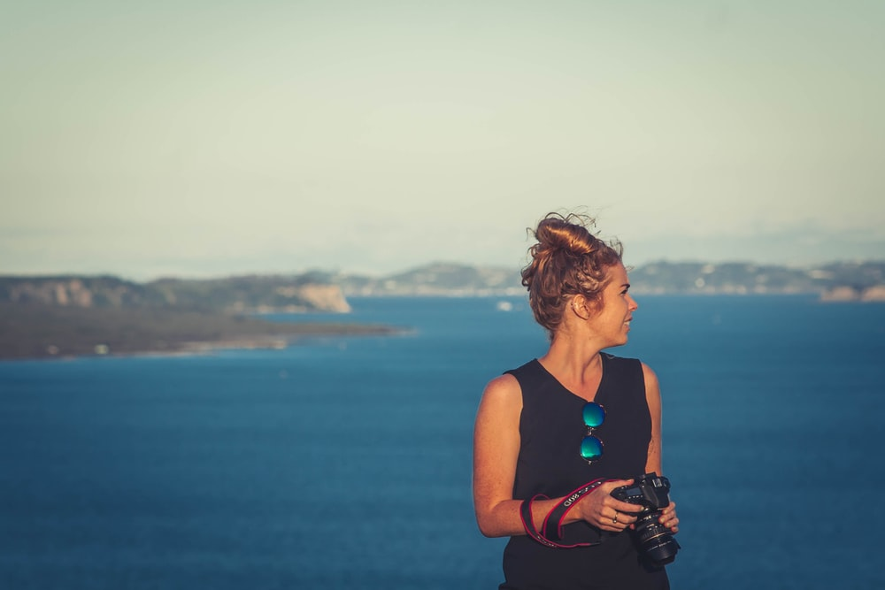 woman wearing black V-neck sleeveless dress holding DSLR camera in front of sea