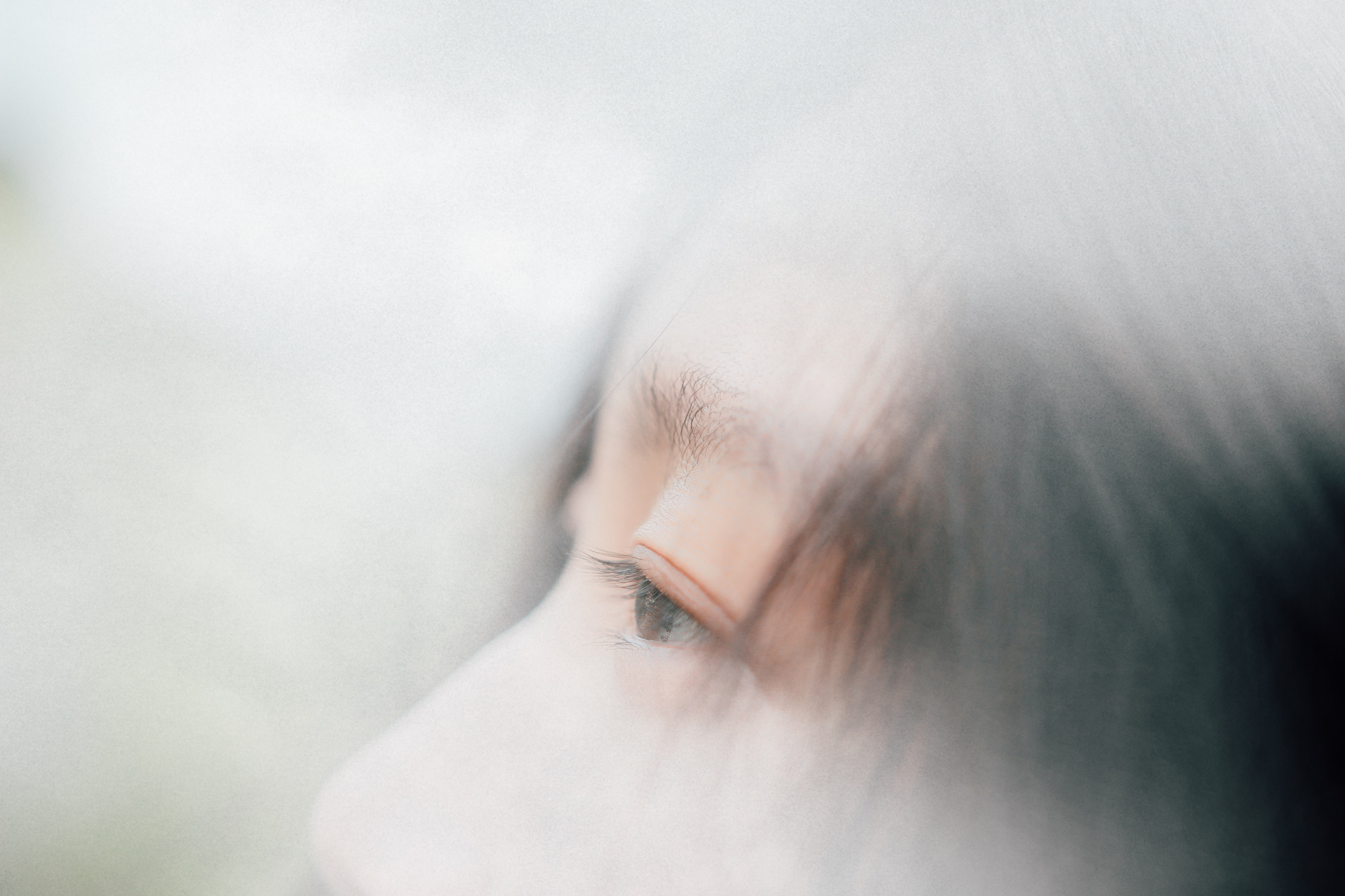 Part of a person's eyes, nose, and face covered in fog and smoke