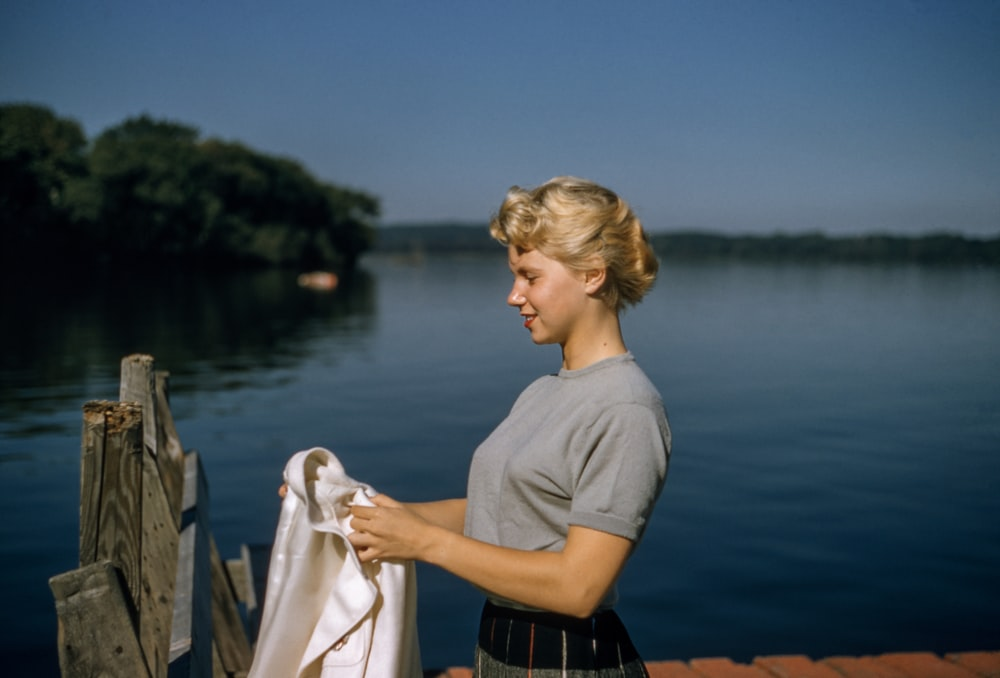 woman holding white textile standing beside body of water