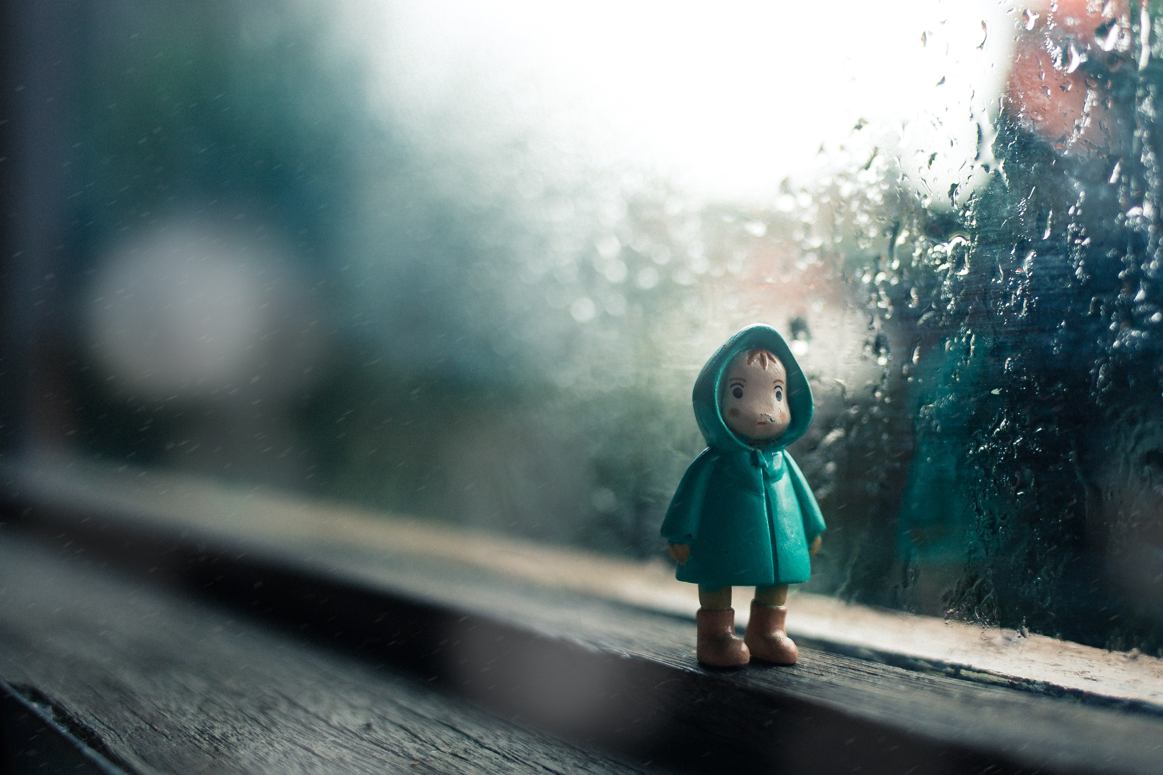 A little figure toy sitting in front of a window on a rainy day in Indonesia