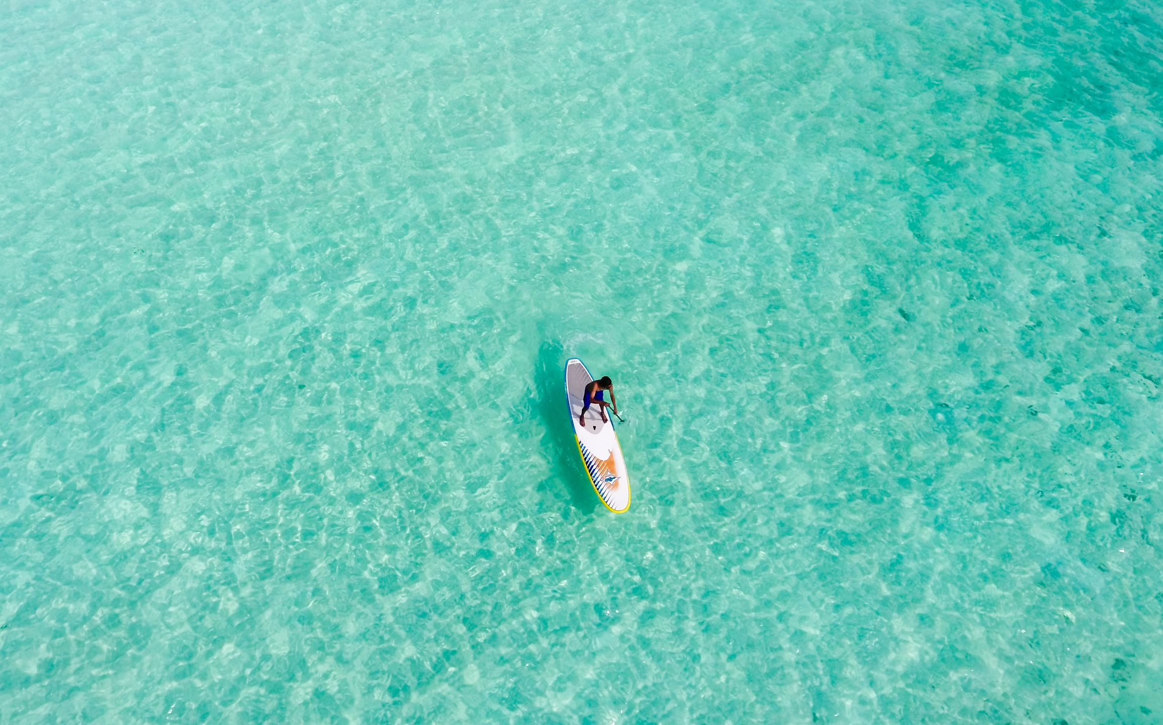 Drone view of a man standing on a paddleboard in the ocean