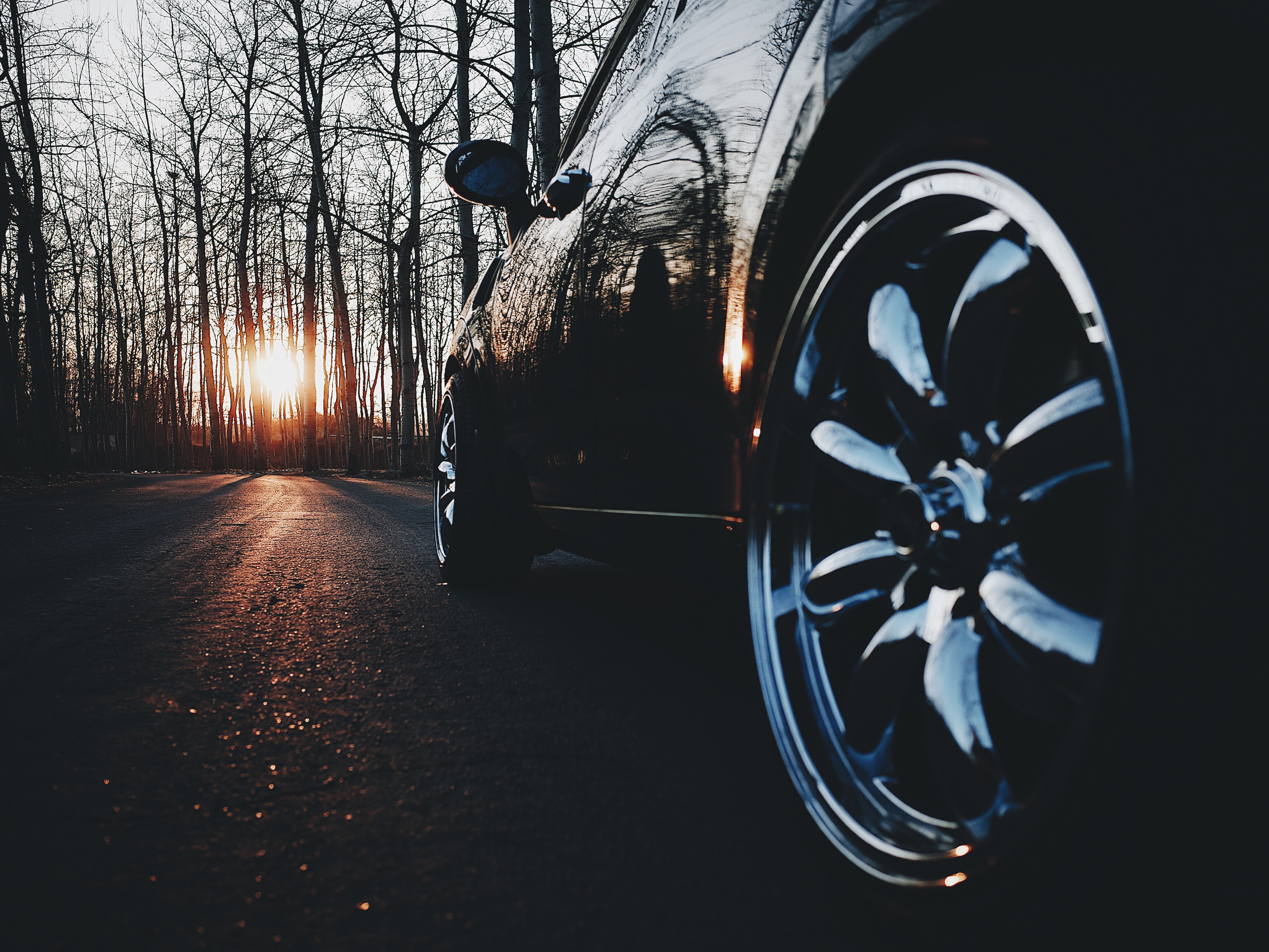 Black car chrome rim on an asphalt road in a leafless forest on sunset