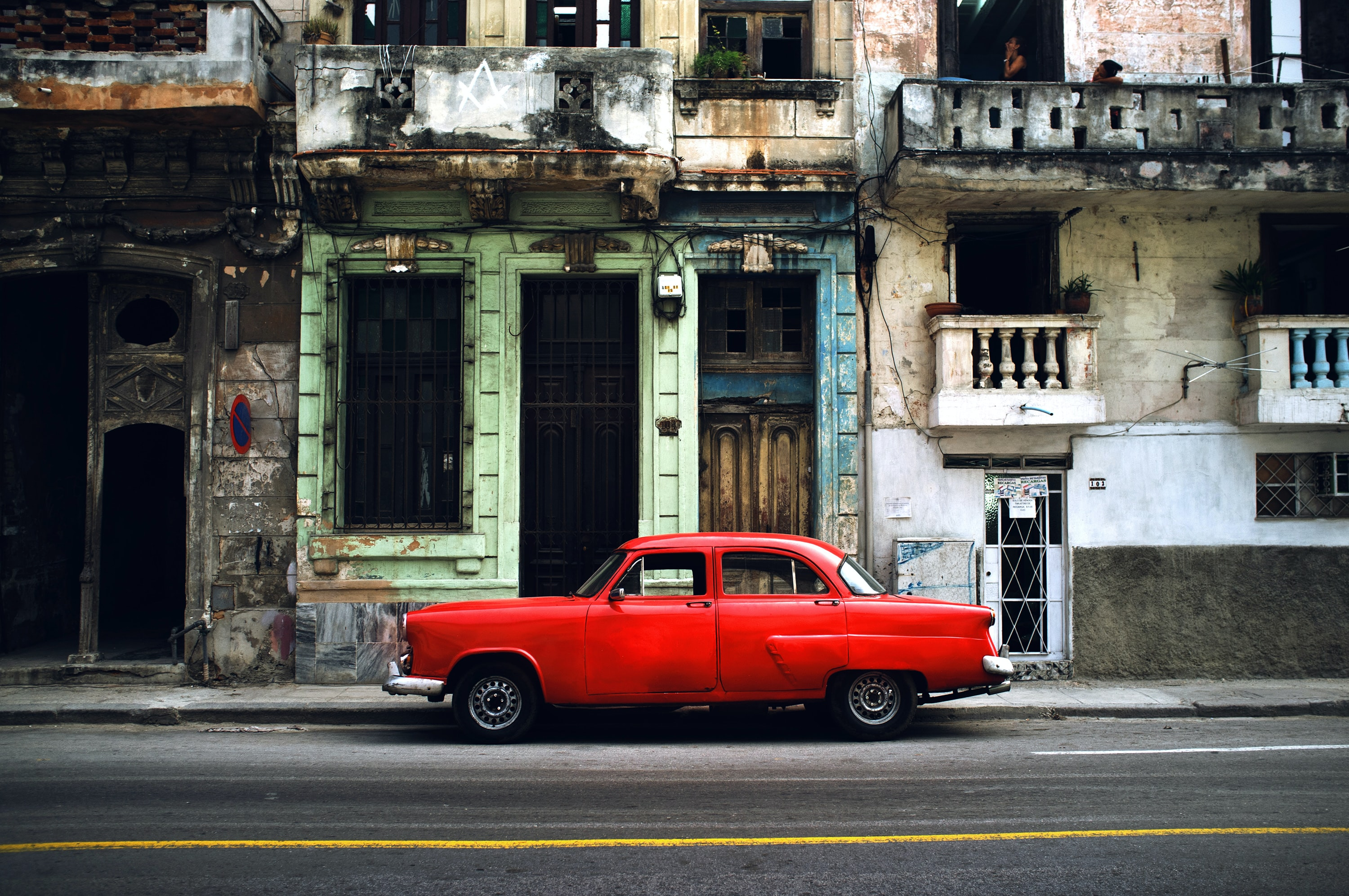 red car parked on road in front concrete building