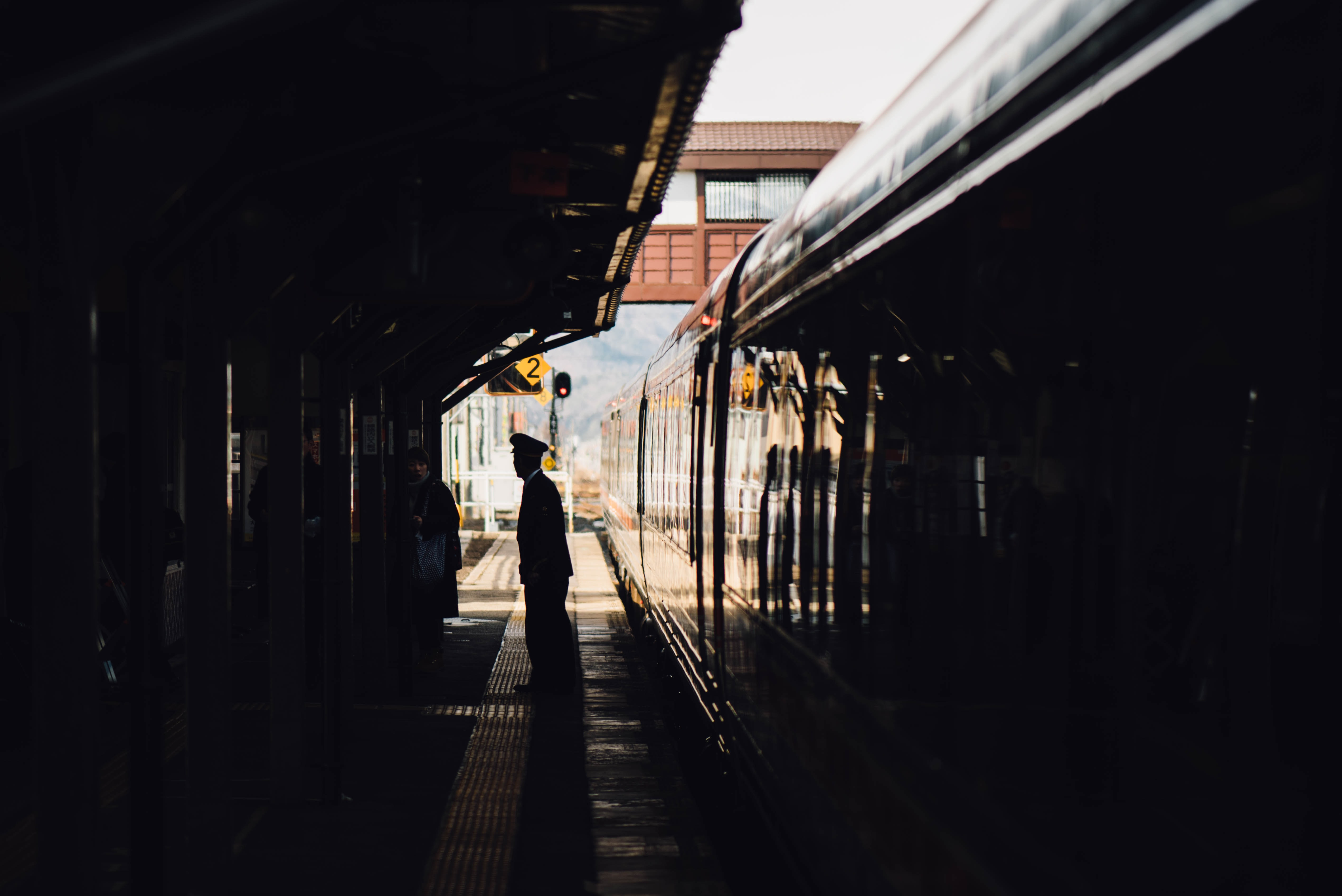 man standing near train in subway during daytime