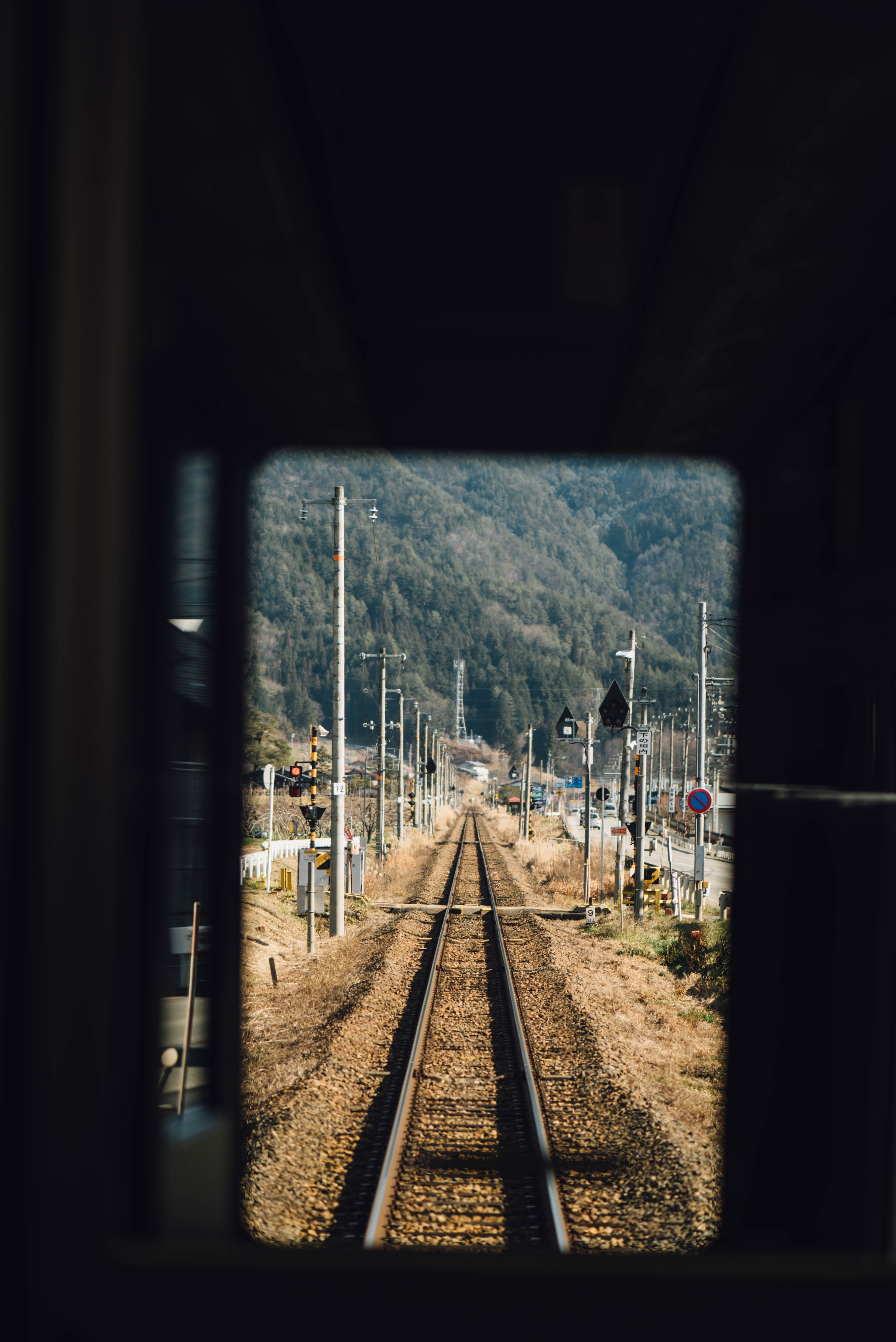 shallow focus photography of train rail near utility poles during daytime