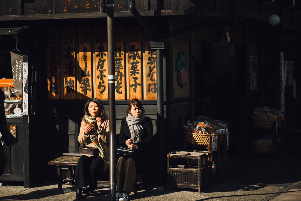 two women sitting on bench outdoor during daytime