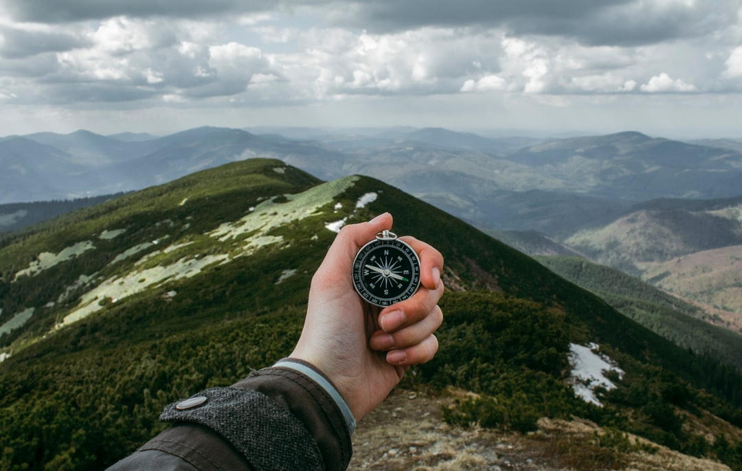A person holding a compass while standing on a ridge in the Carpathian Mountains
