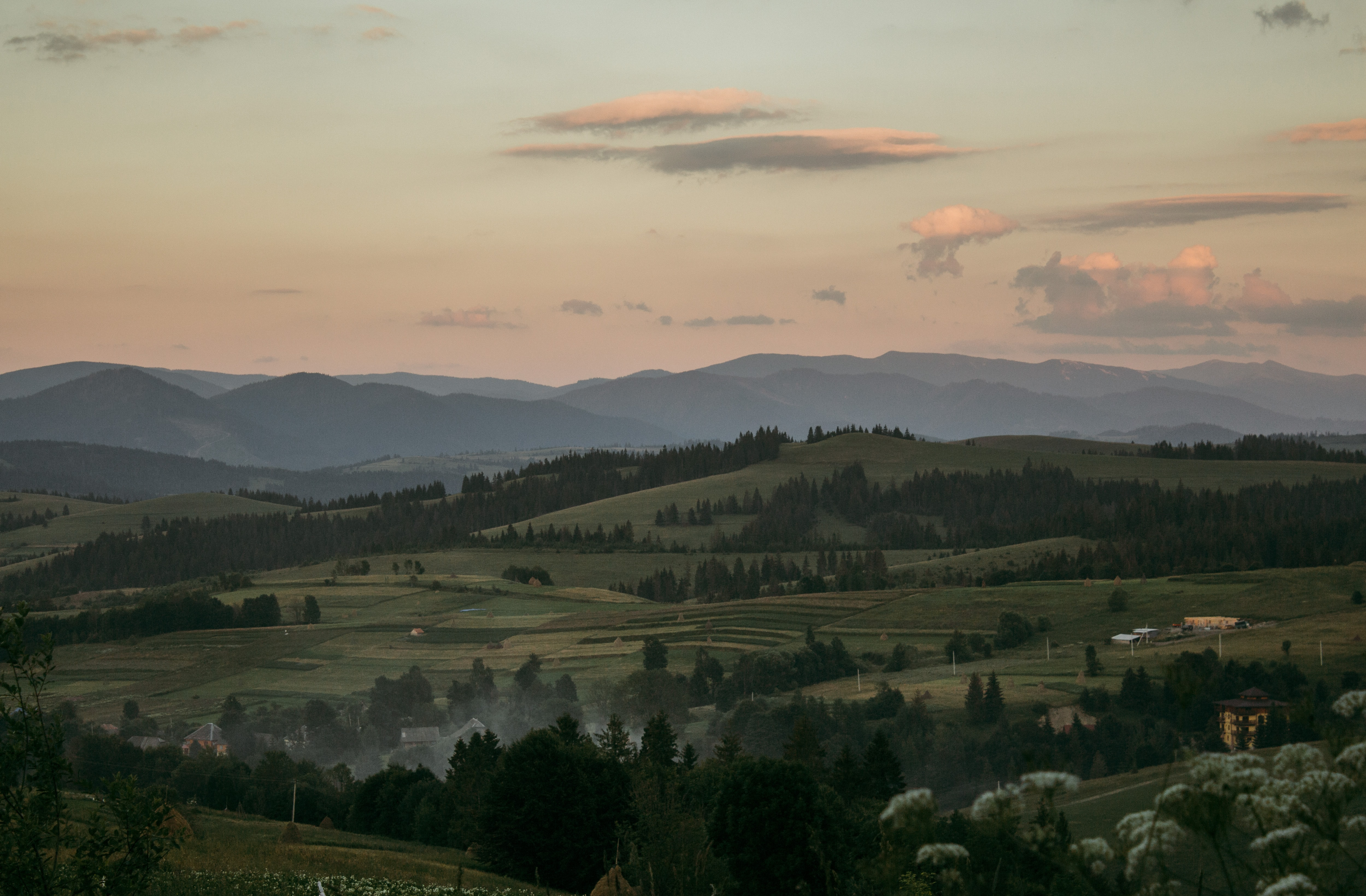 A rural landscape stretching along undulating hills in the Carpathian Mountains