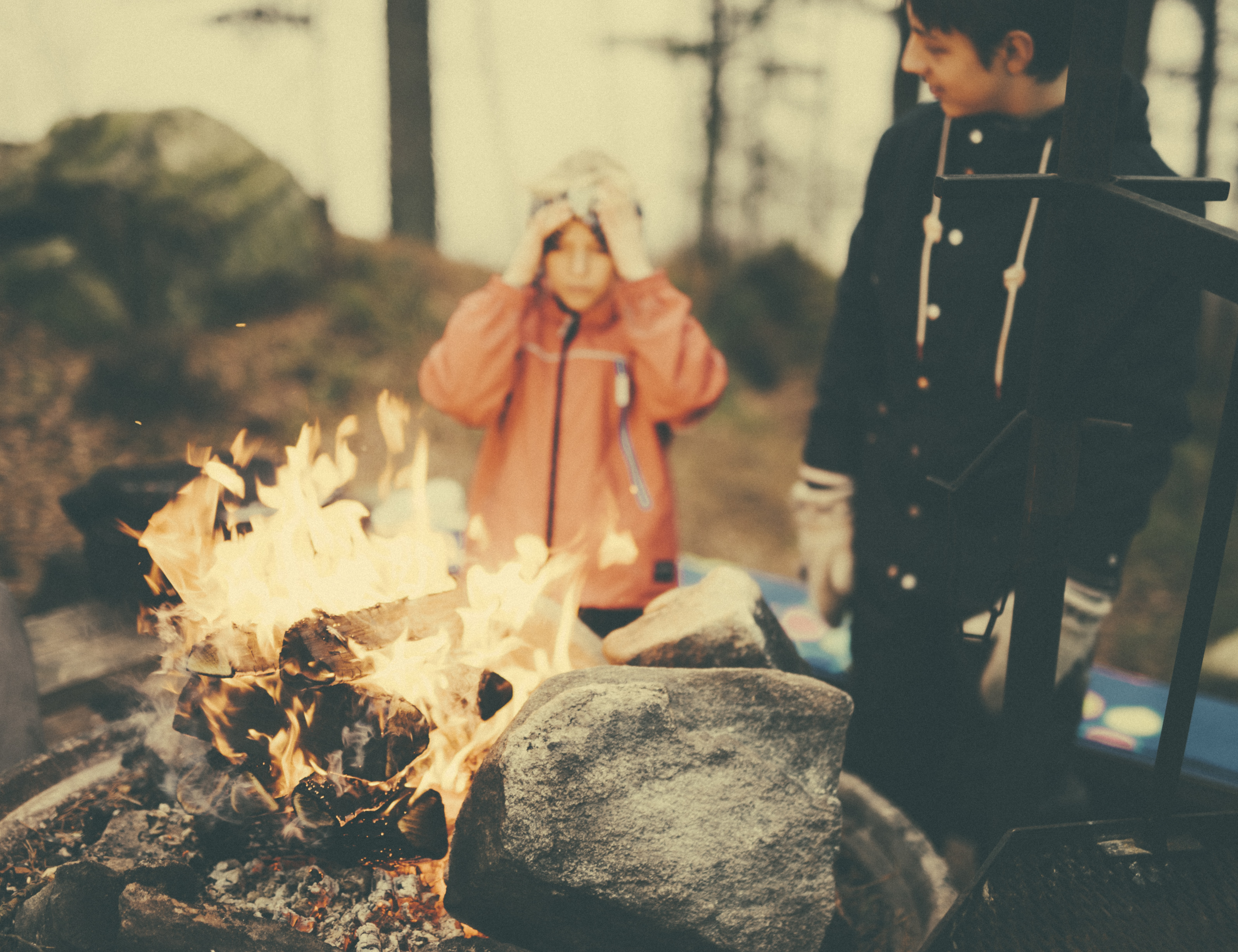 A child and teenager stand near a fire in Borås