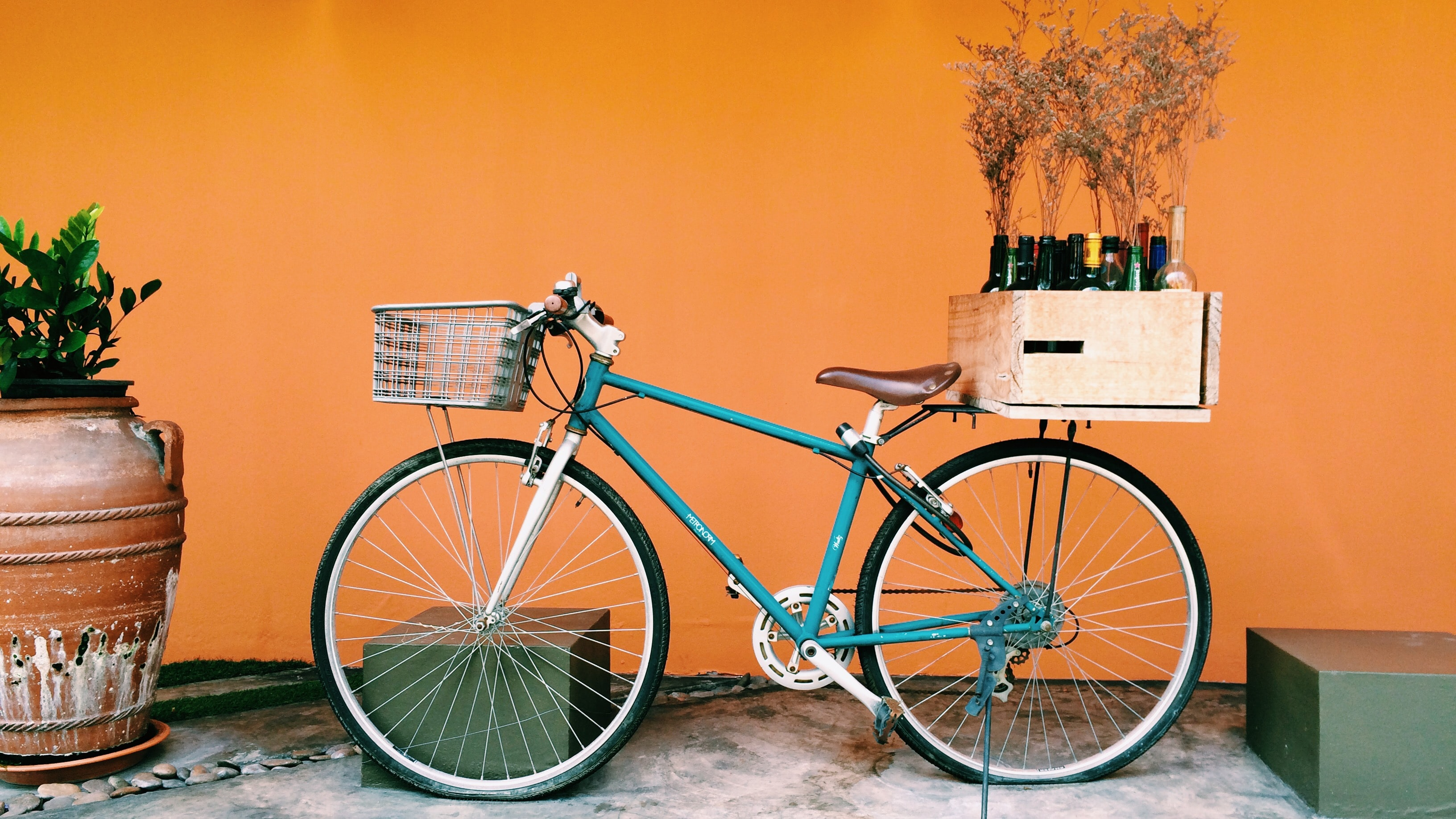 A bicycle with a crate of wine on its carrier against an orange wall