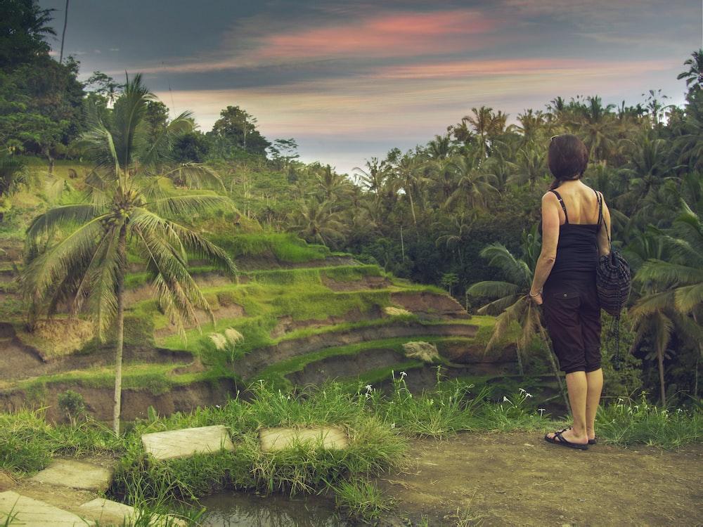 woman standing wearing black cami top during daytime