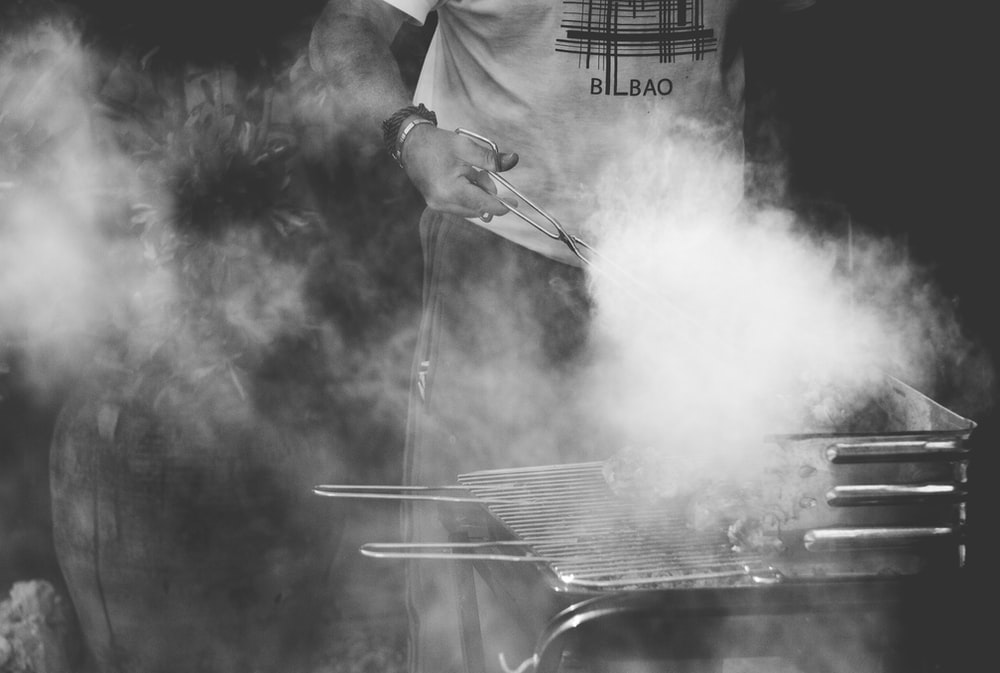 grayscale photo of man standing near gas grill