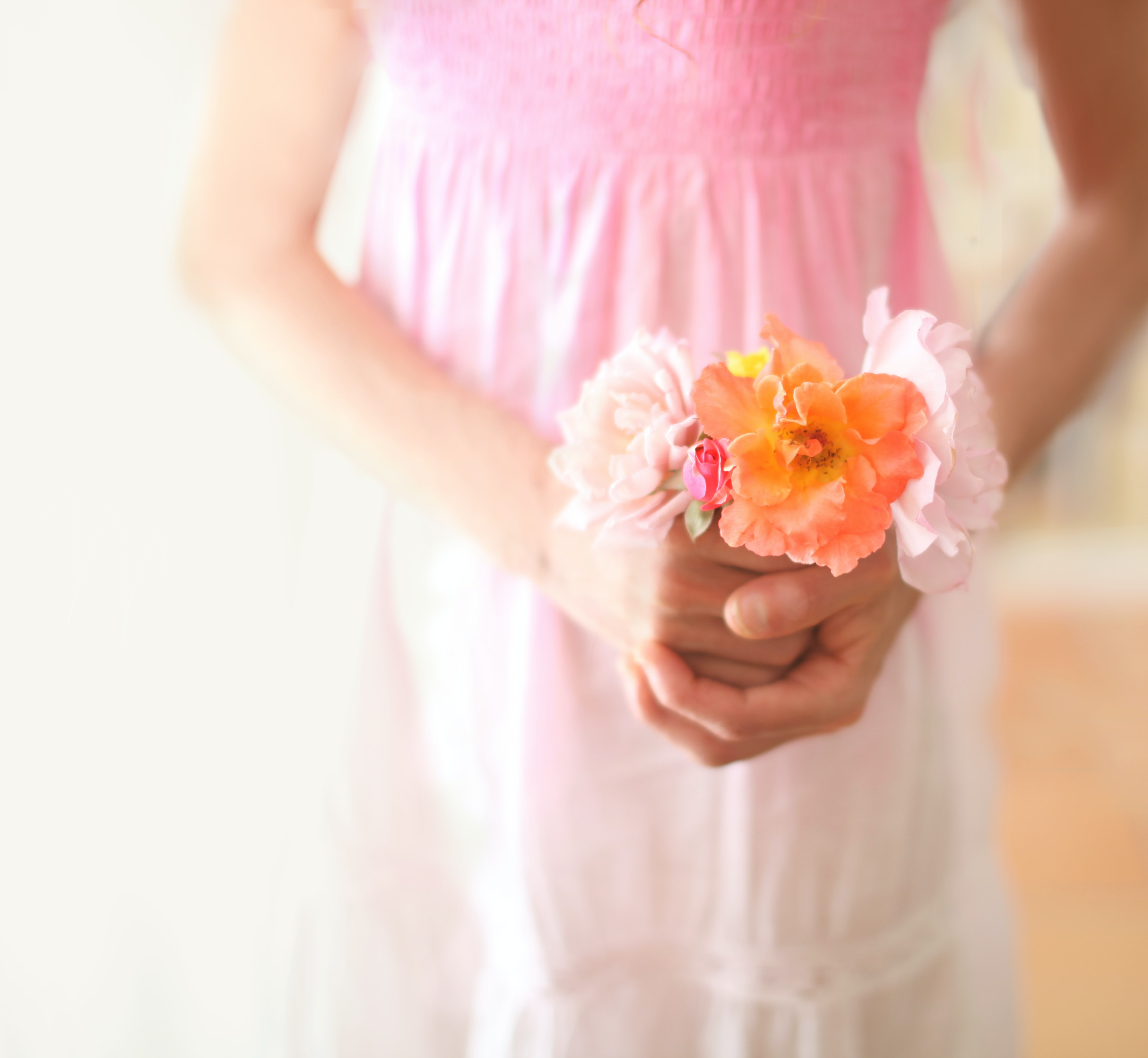 A girl holding a bouquet of white, pink and orange flowers in front of her dress