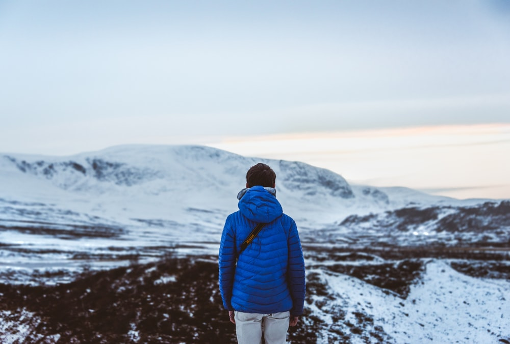 person in blue hoodie facing snow covered hill