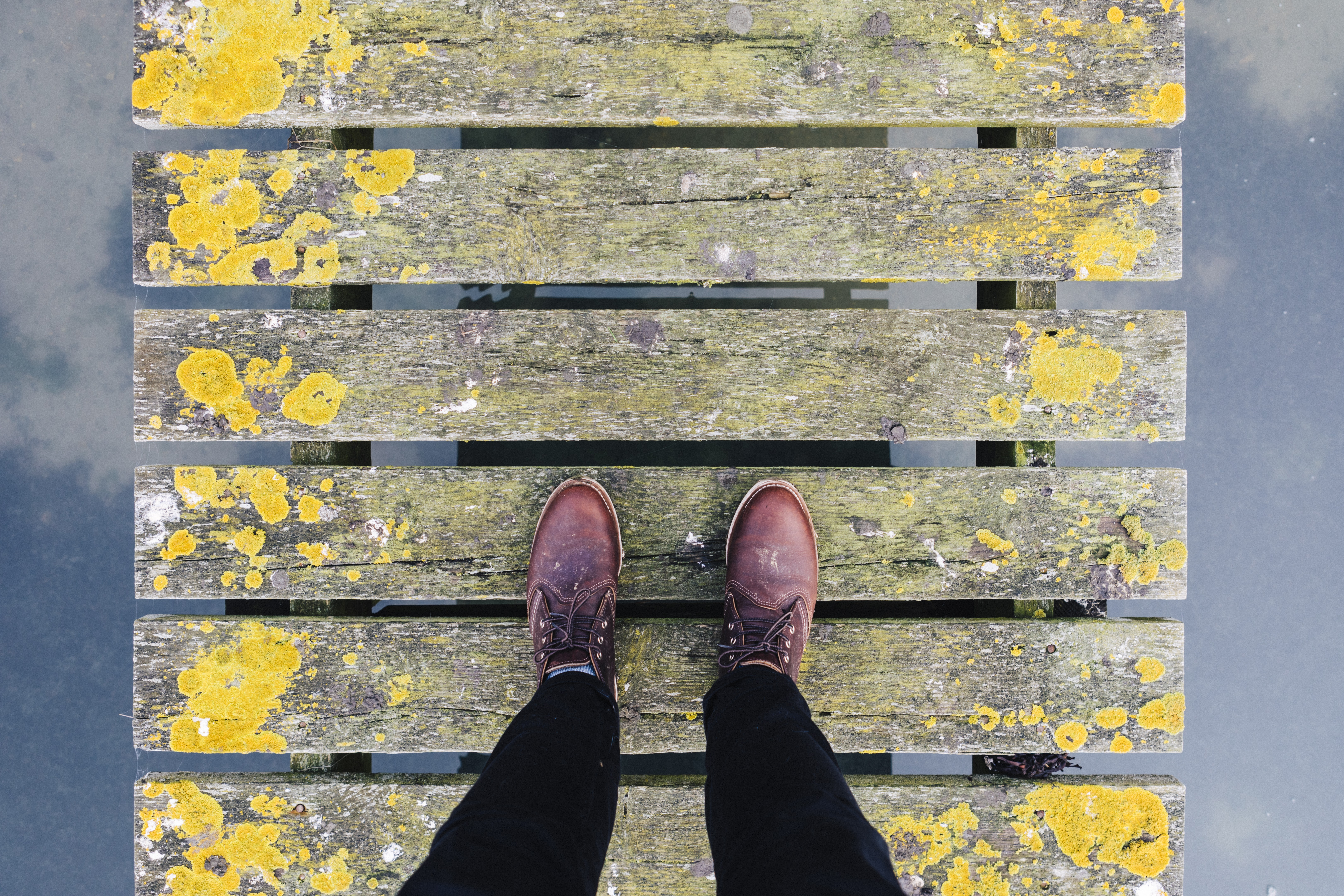 A person wearing burgundy color footwear walking on a fence style bridge