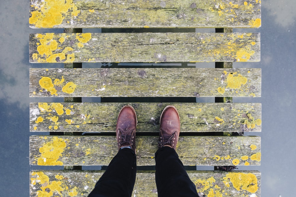 pair of brown leather shoes standing on grey and yellow bridge