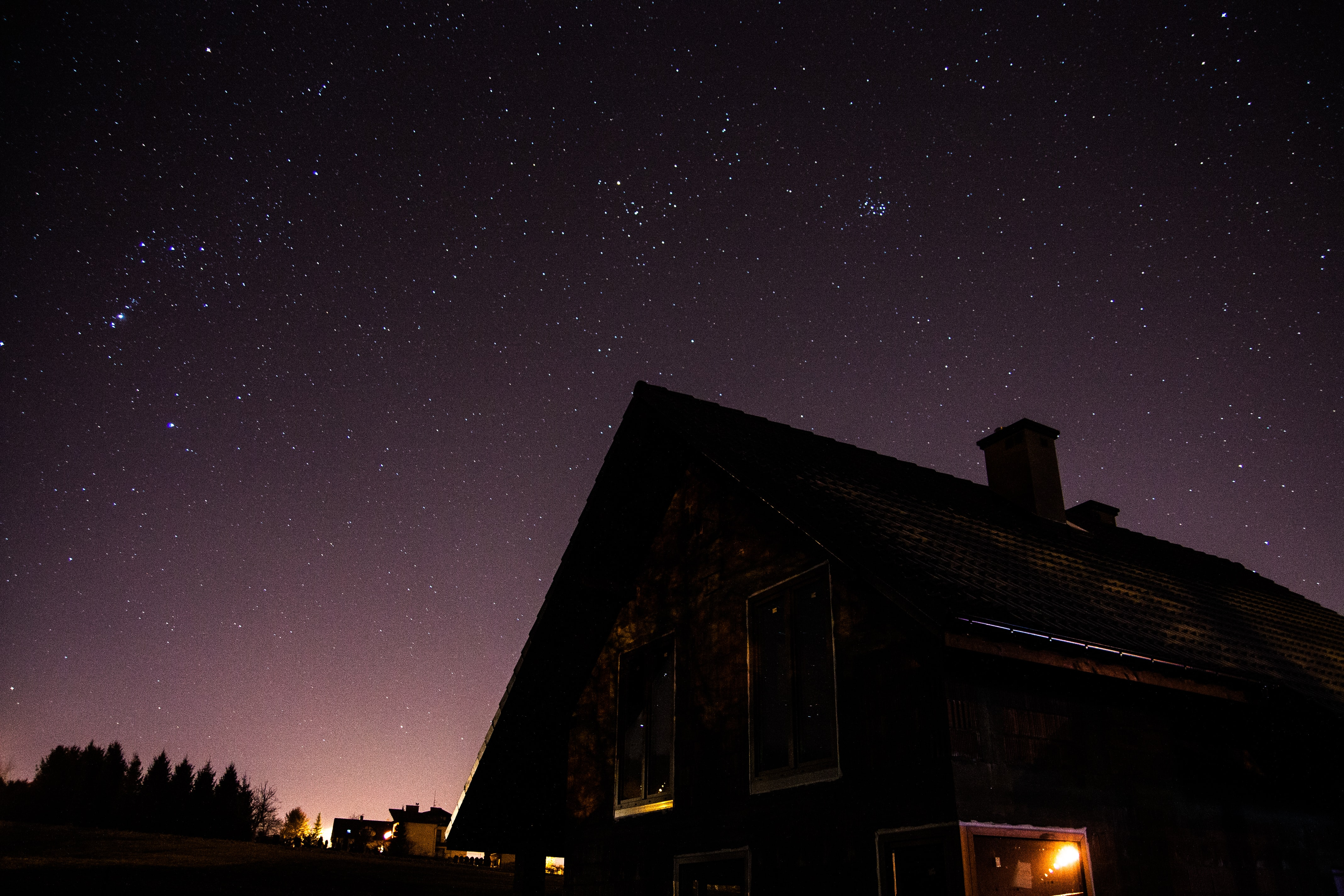Silhouette of a house at night with stars in a dark sky
