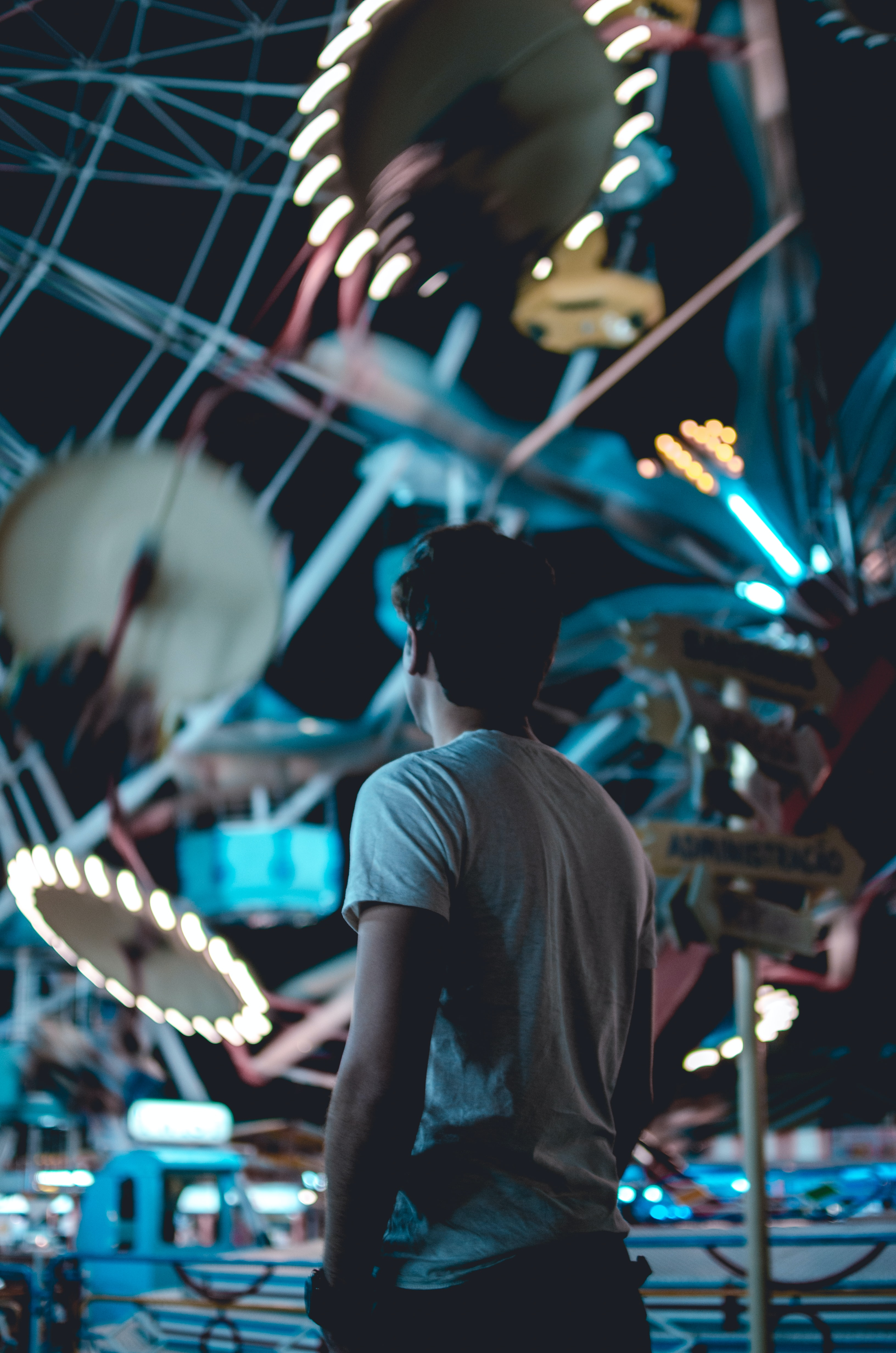 A man stares up at a lit up ride at the fairground in Belo Horizonte, Brazil