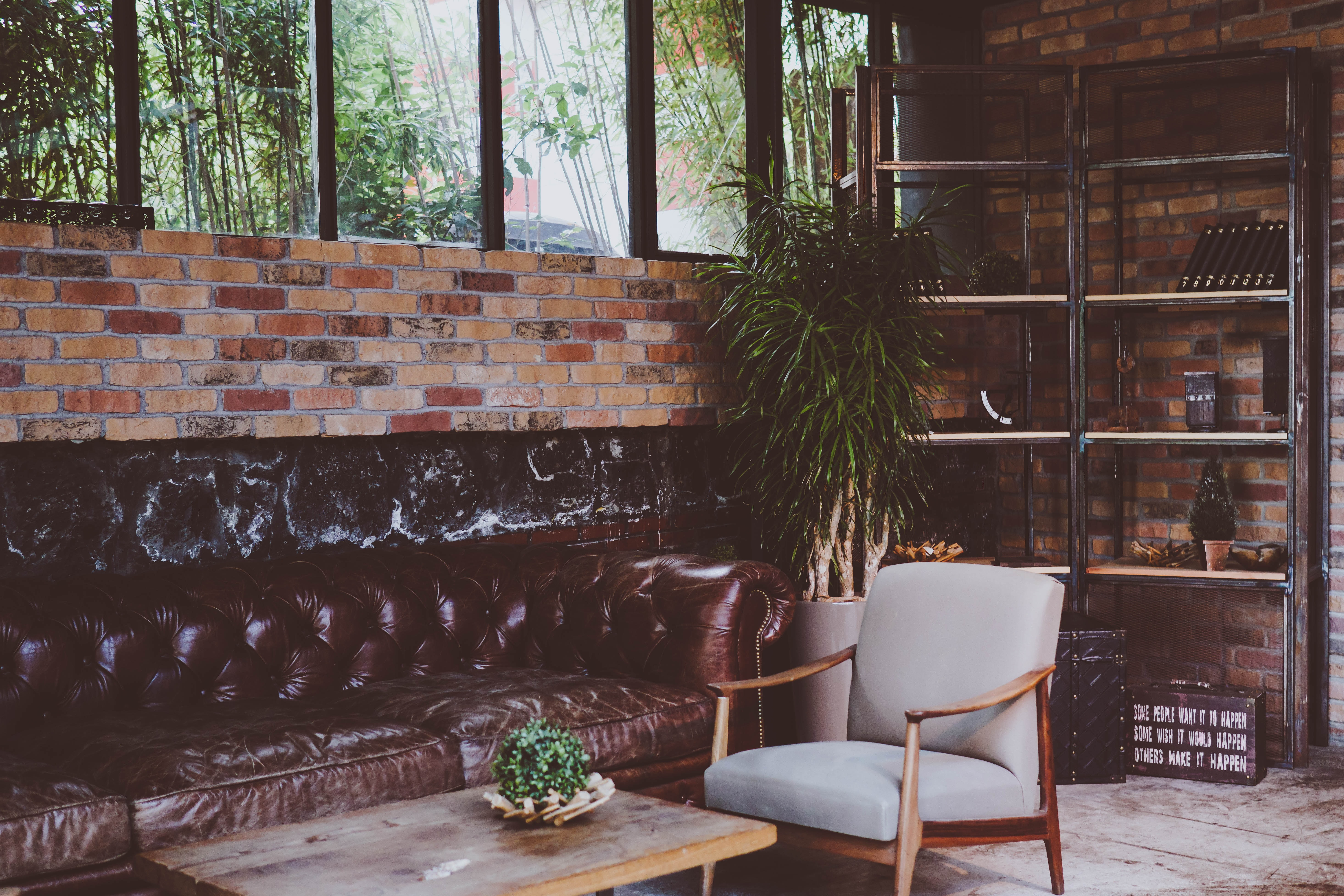 A living room with brick walls, a leather quilted sofa, steel bookshelf, plants, and coffee table in Istanbul
