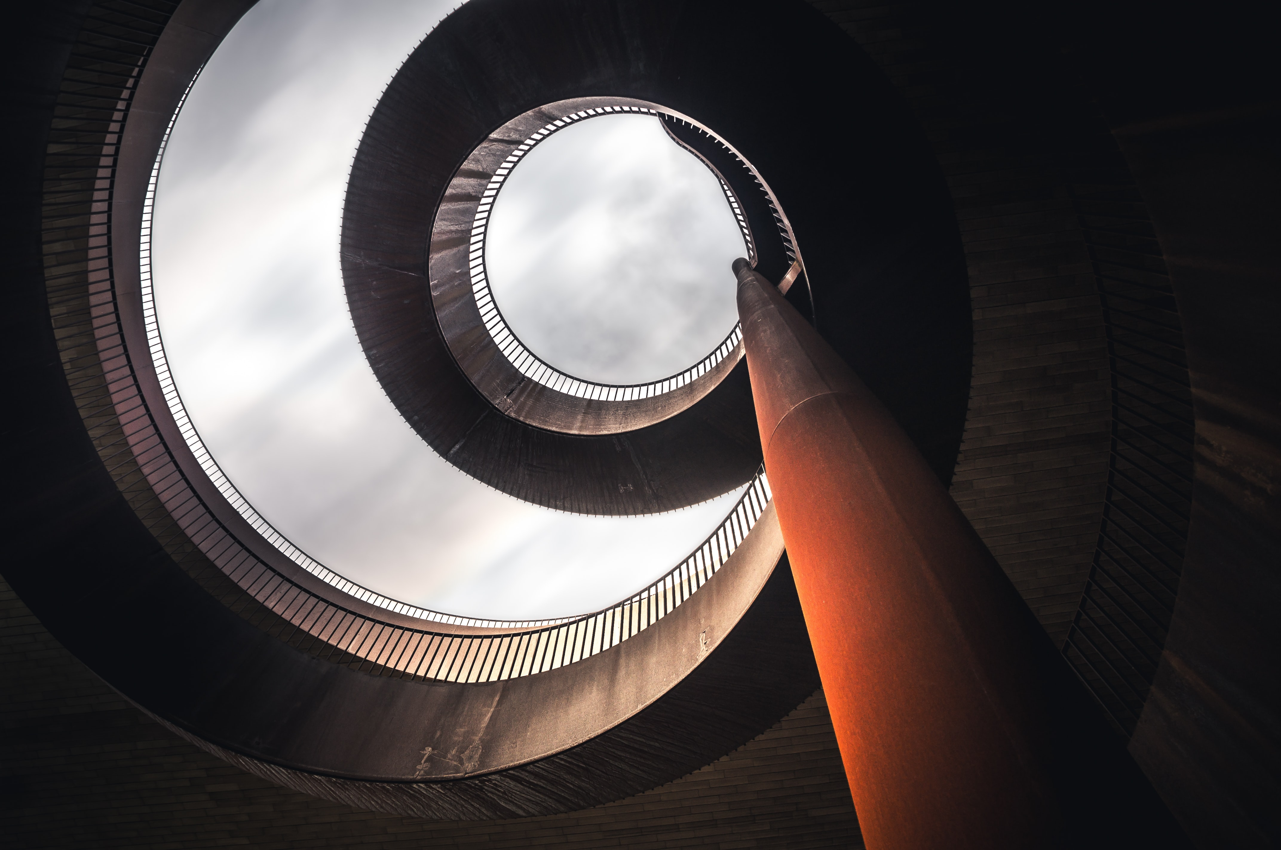 low angle photography of concrete spiral stairs
