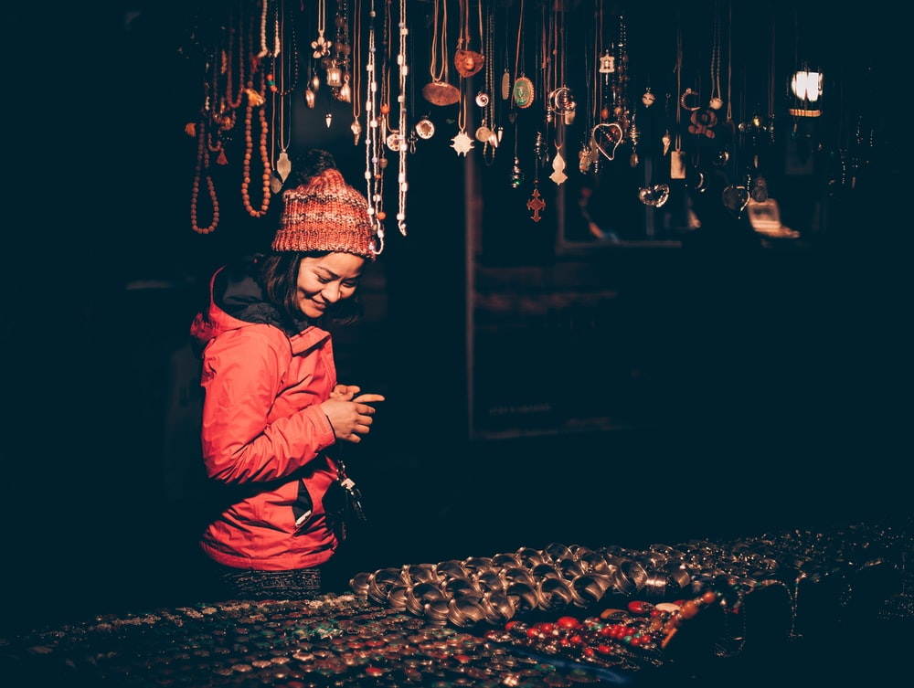 woman looking on assorted jewelr