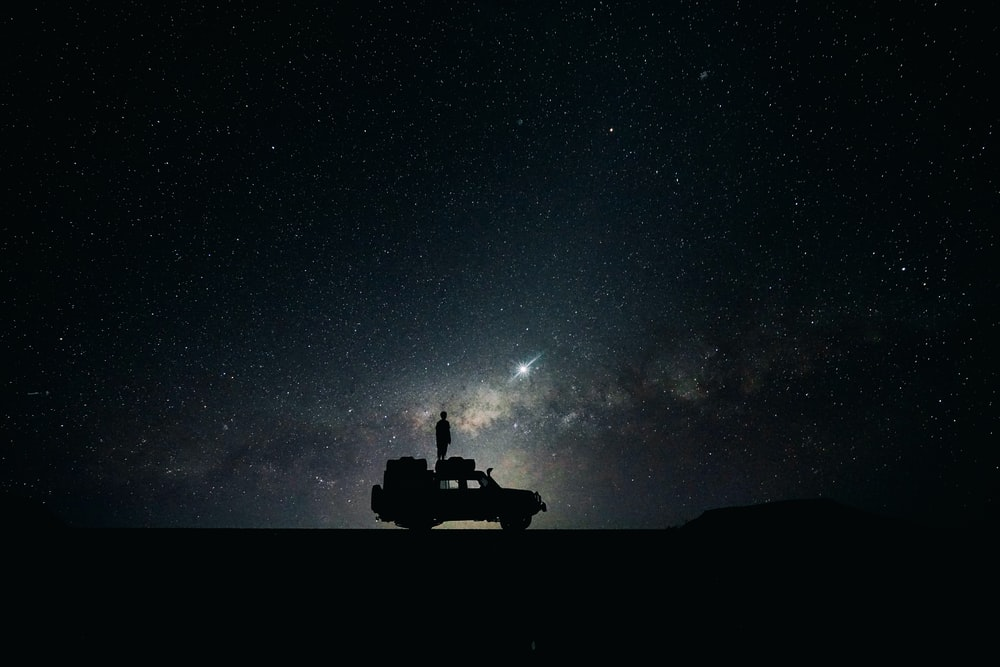 Silhouette Standing On A Jeep Roof Looking At The Starry Night Sky With Nebulas In Sossusvlei