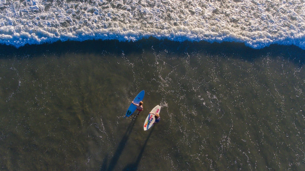 high angle photo of two persons carrying surfboards on seashore