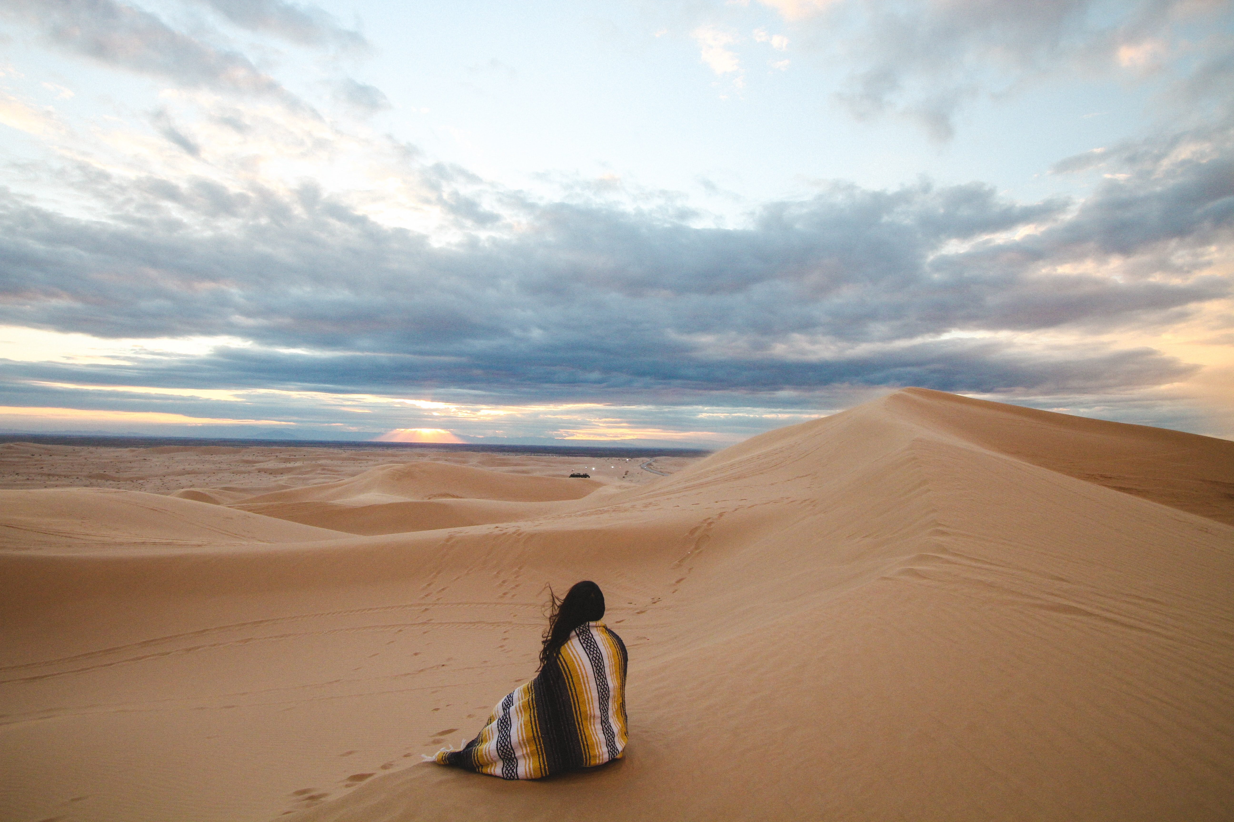 Woman sits in an Aztec blanket watching the desert sunset