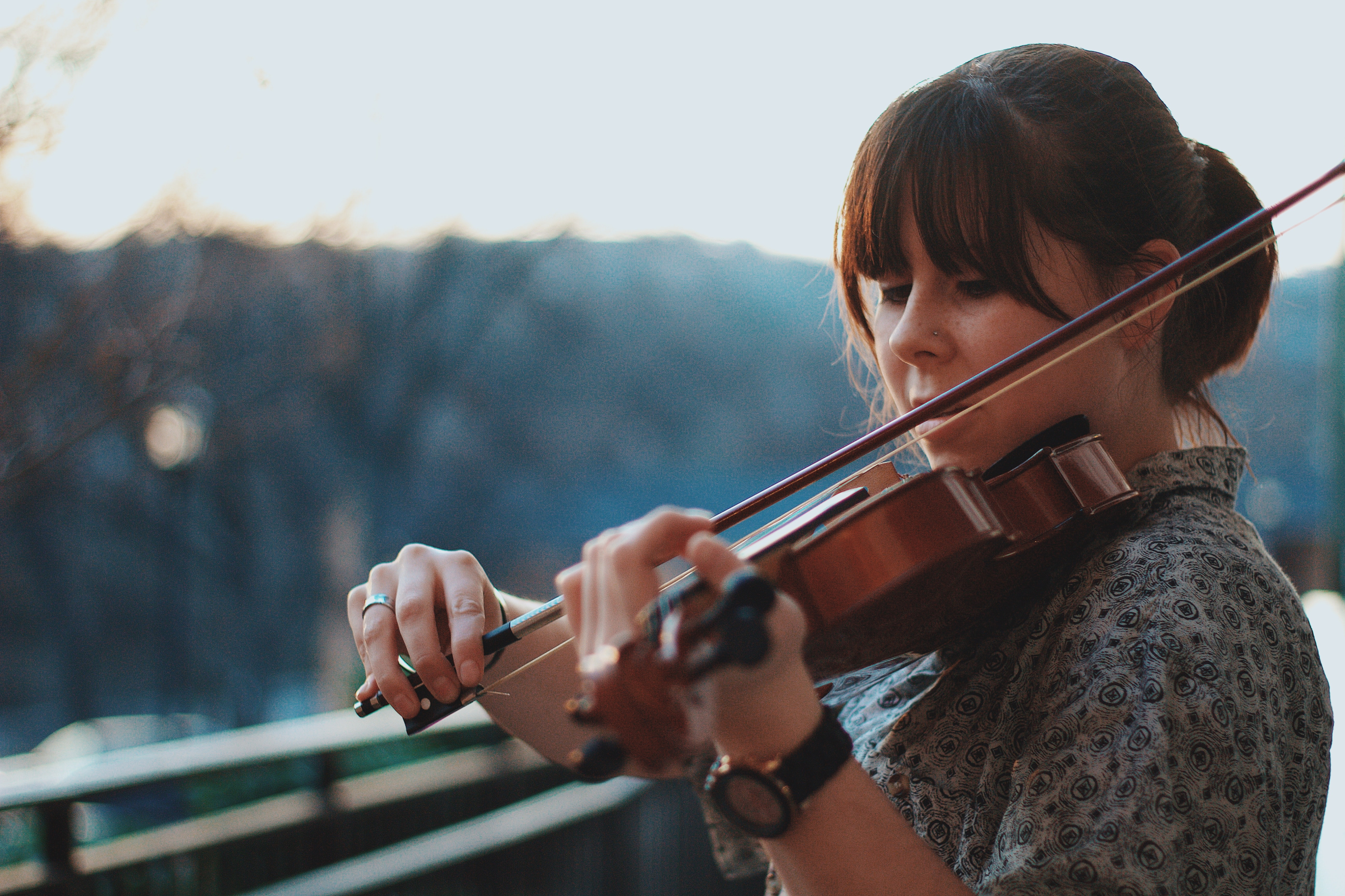 A woman playing a violin outdoors
