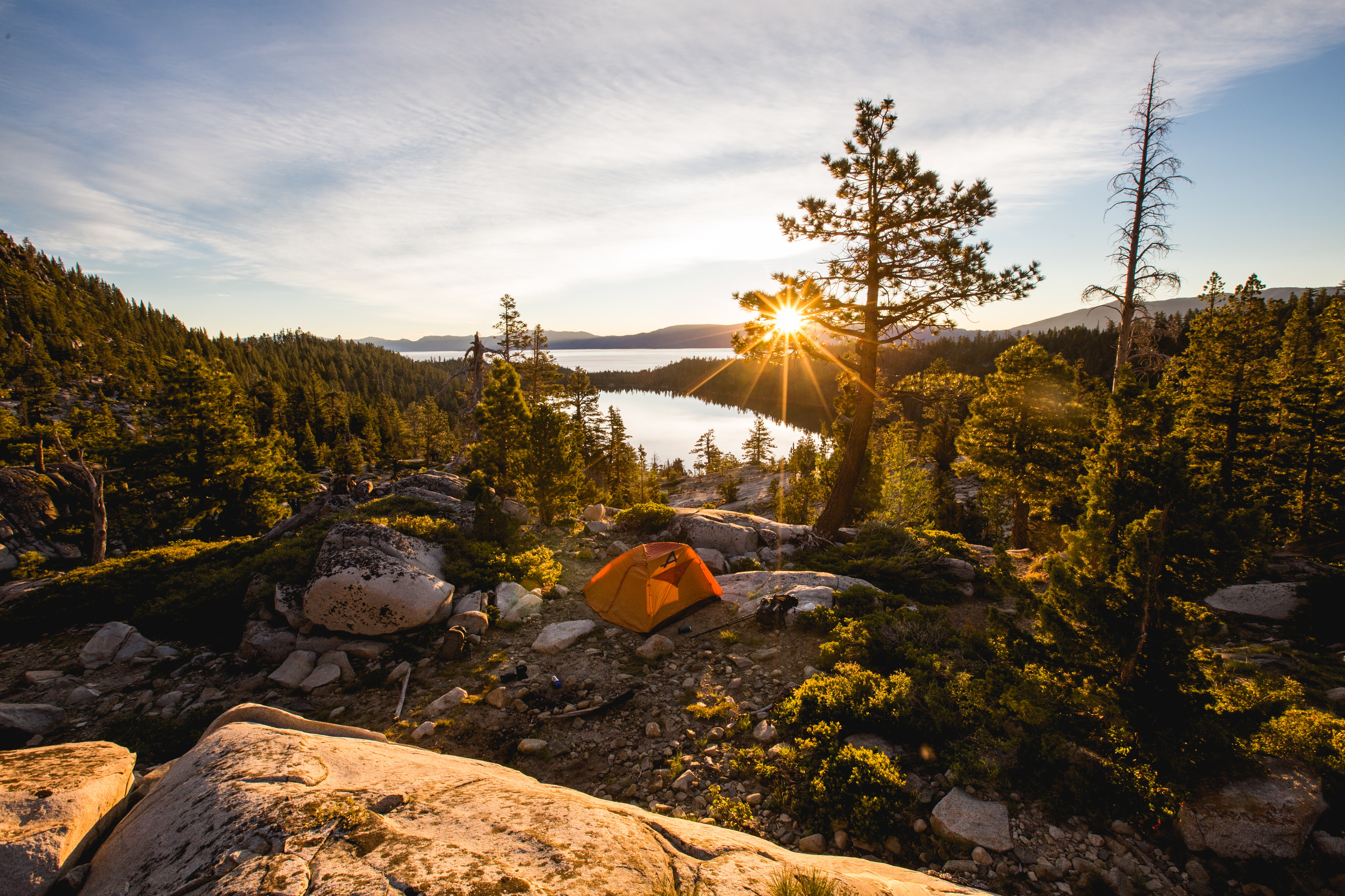 A sunrise view of a lake and forest from a mountain